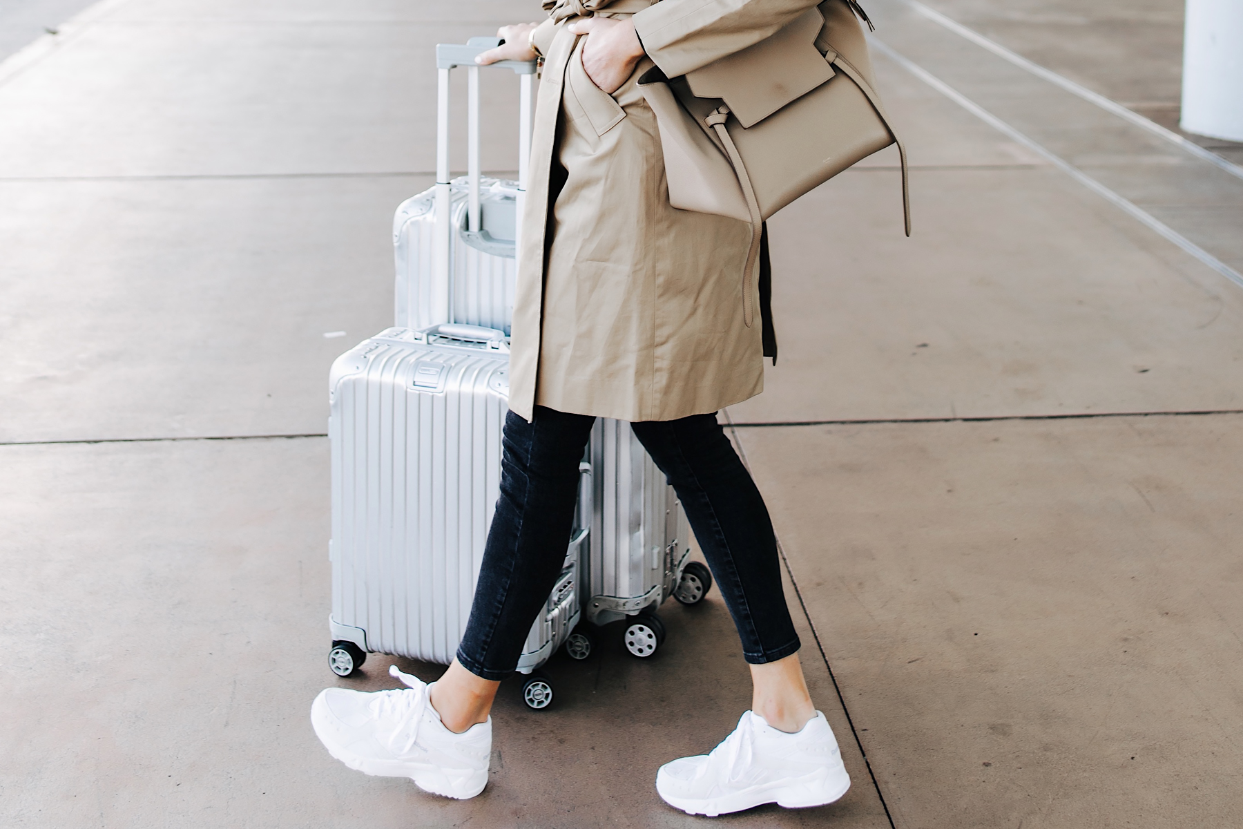 Woman Wearing Airport Travel Outfit Trench Coat Black Skinny Jeans Reebok Aztrek White Sneakers Rimowa Luggage Fashion Jackson San Diego Fashion Blogger Street Style