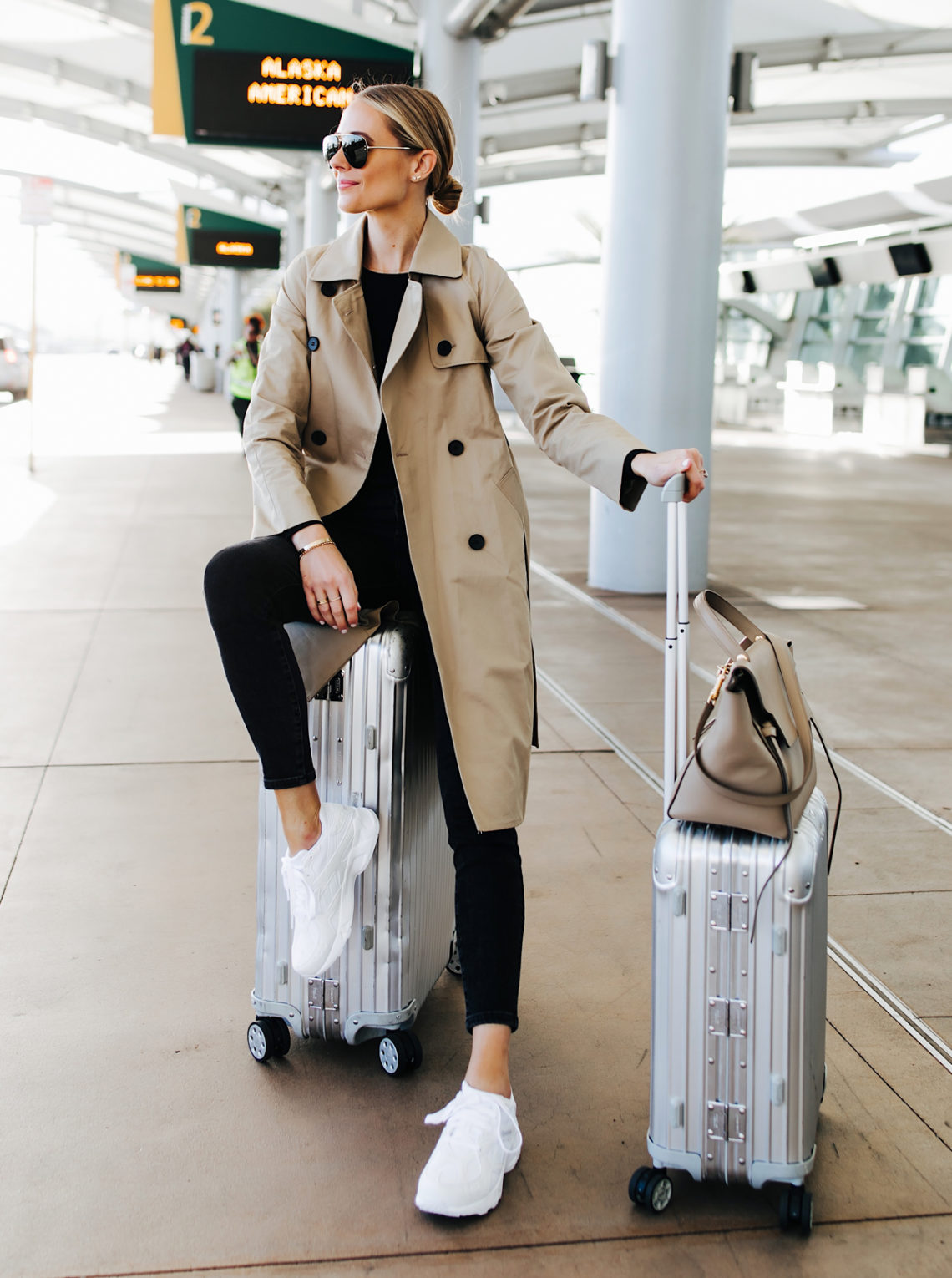 Fashion Jackson Airport Travel Outfit Trench Coat Black Skinny Jeans Reebok Aztrek White Sneakers Rimowa Luggage Featured Image