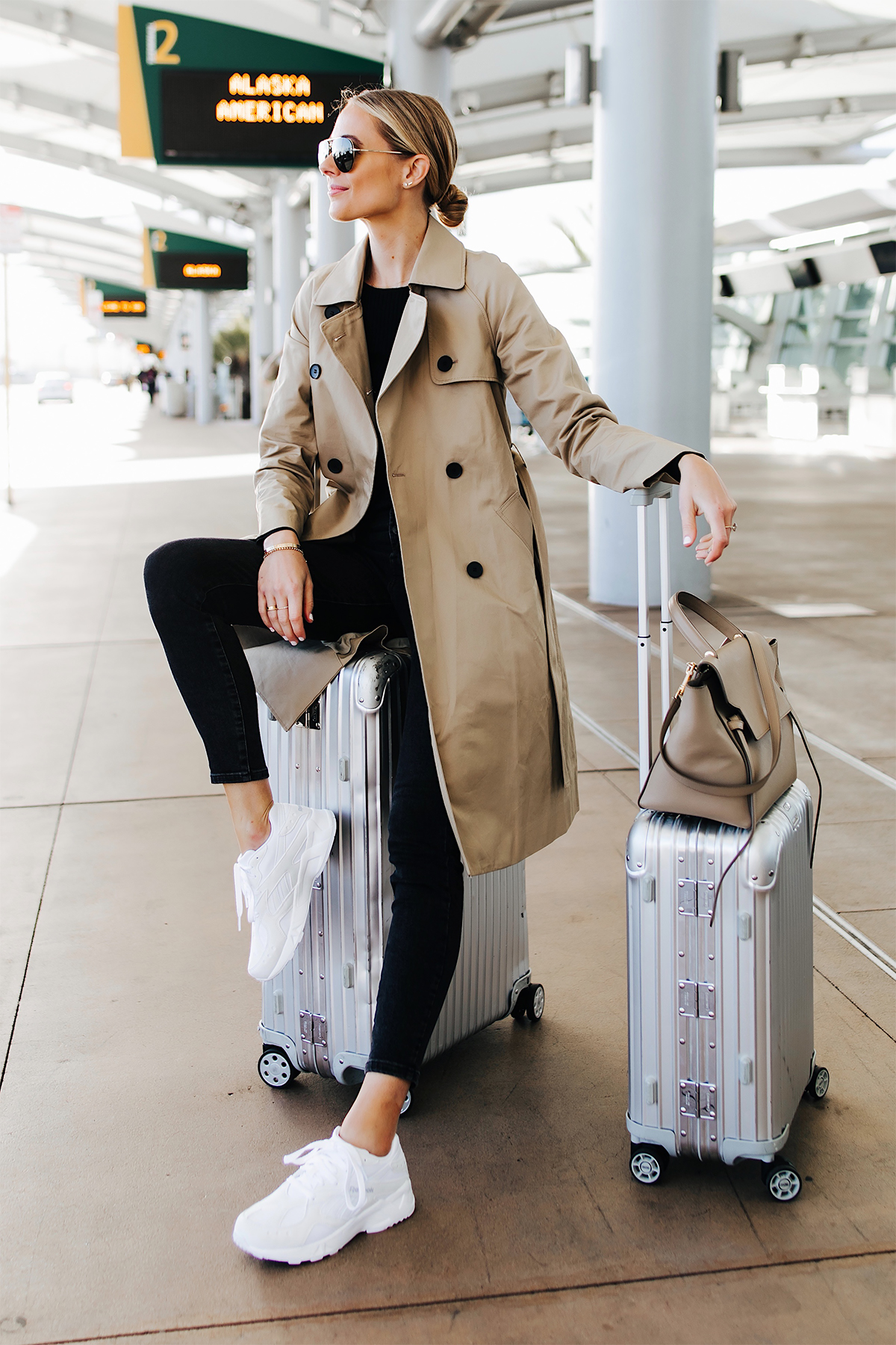 Blonde Woman Wearing Airport Travel Outfit Trench Coat Black Skinny Jeans Reebok Aztrek White Sneakers Rimowa Luggage Fashion Jackson San Diego Fashion Blogger Street Style