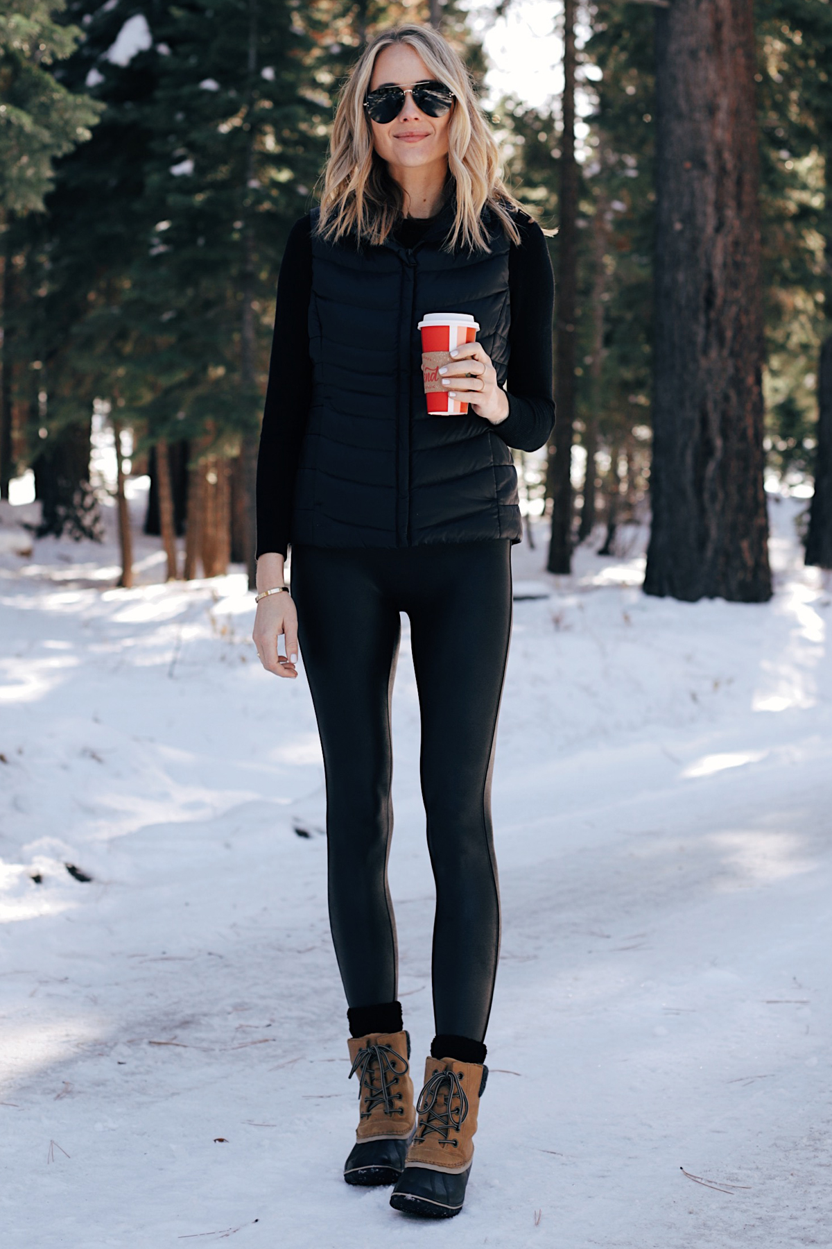 Fashion-Jackson-Wearing-Black-Puffer-Vest-Black-Spanx-Faux-Leather-Leggings-Sorel-Snow-Boots-Winter-Outfi