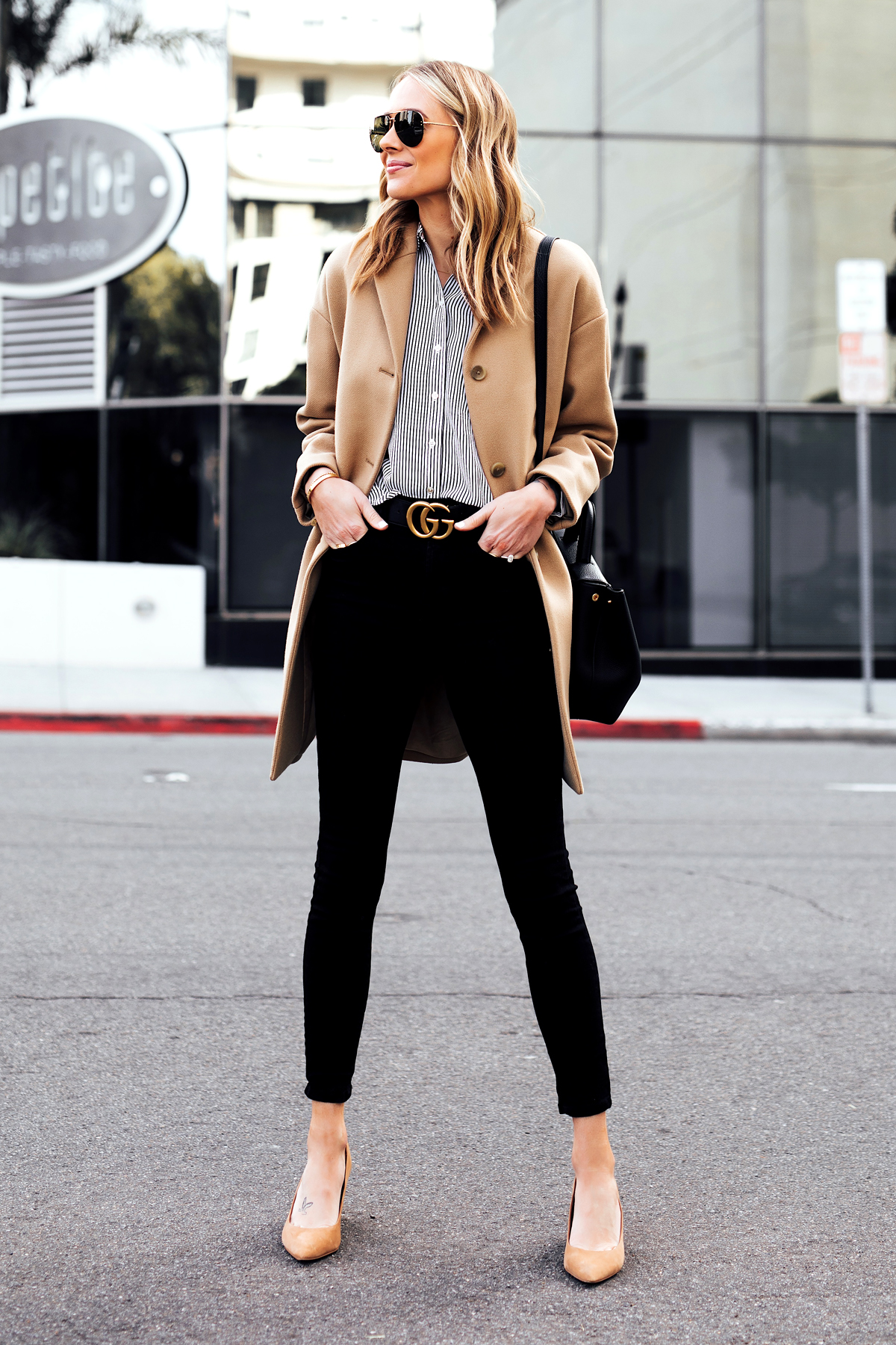 Blonde Woman Wearing Everlane Camel Coat Black White Stripe Button Down Shirt Black Skinny Jeans Black Gucci Belt Tan Pumps Fashion Jackson San Diego Fashion Blogger Street Style