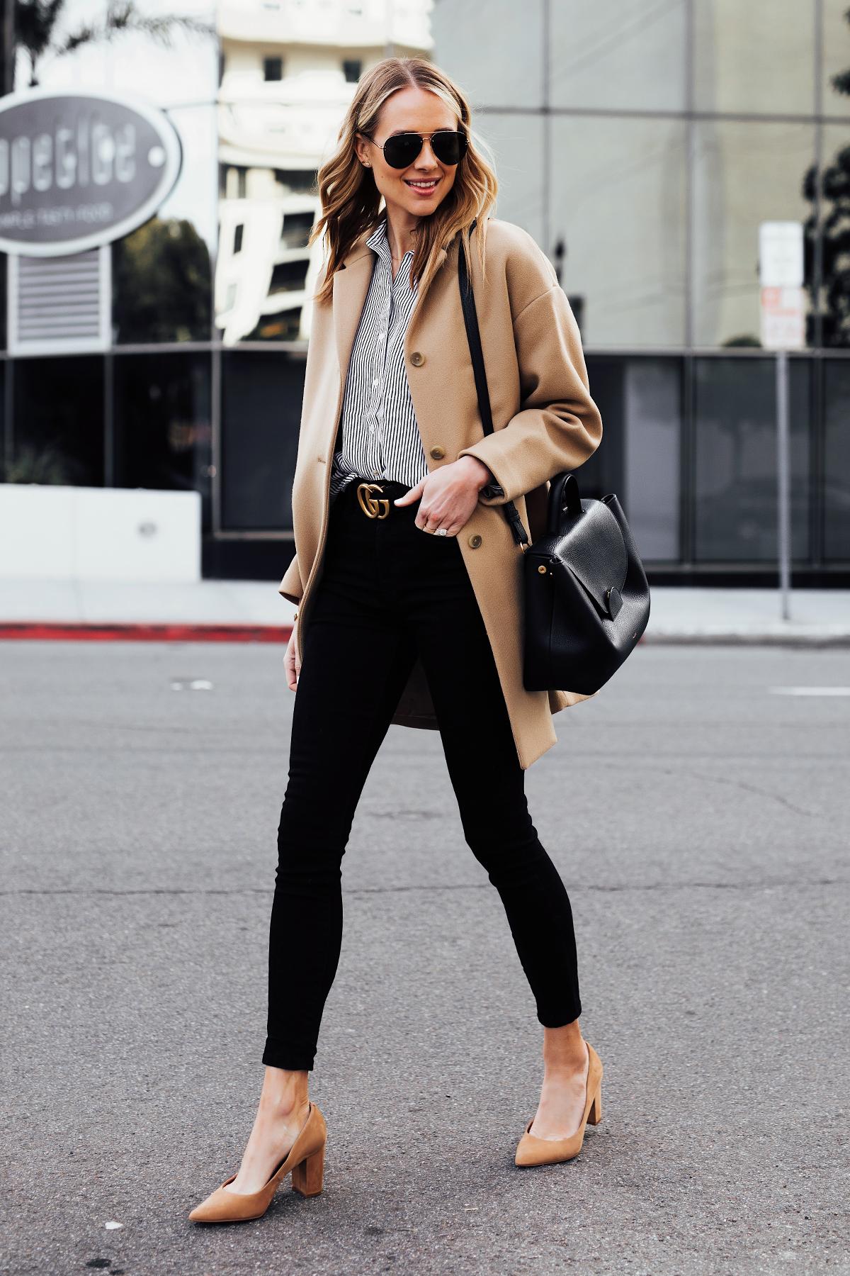 a3264516dae Blonde Woman Wearing Everlane Camel Coat Black White Stripe Button Down  Shirt Black Skinny Jeans Black