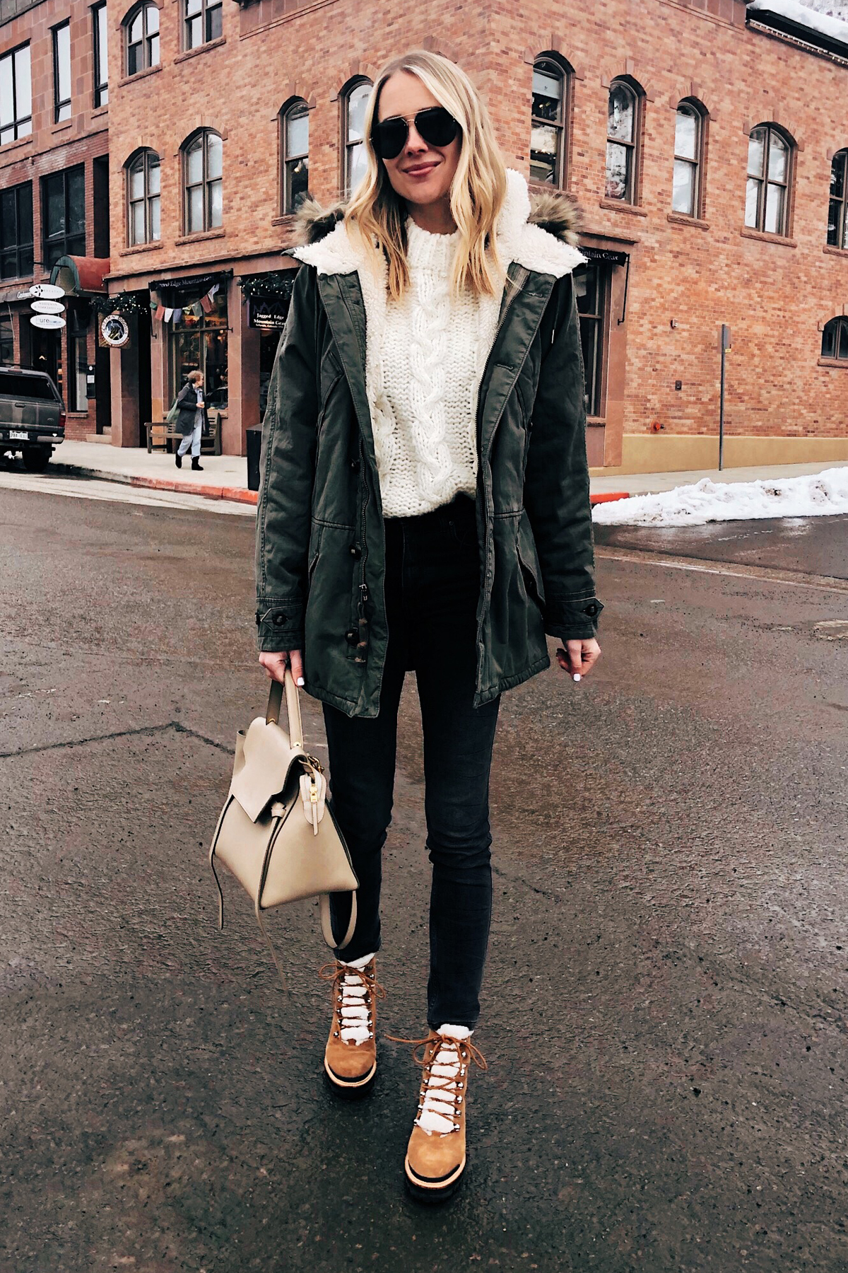 Fashion-Jackson-Wearing-Green-Parka-White-Knit-Sweater-Black-Jeans-Marc-Fisher-Winter-Boots