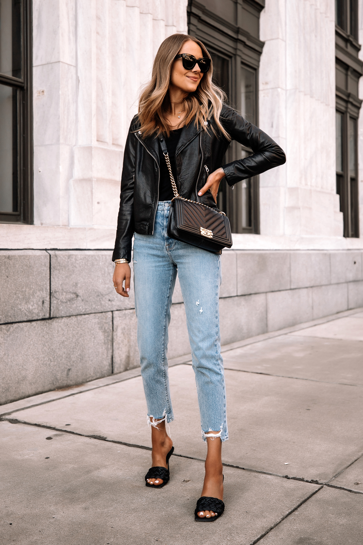 Fashion Jackson Wearing Madewell Black Leather Jacket Black Bodysuit Ripped Jeans Black Woven Heeled Sandals Chanel Black Boy Bag Street Style Outfit 1