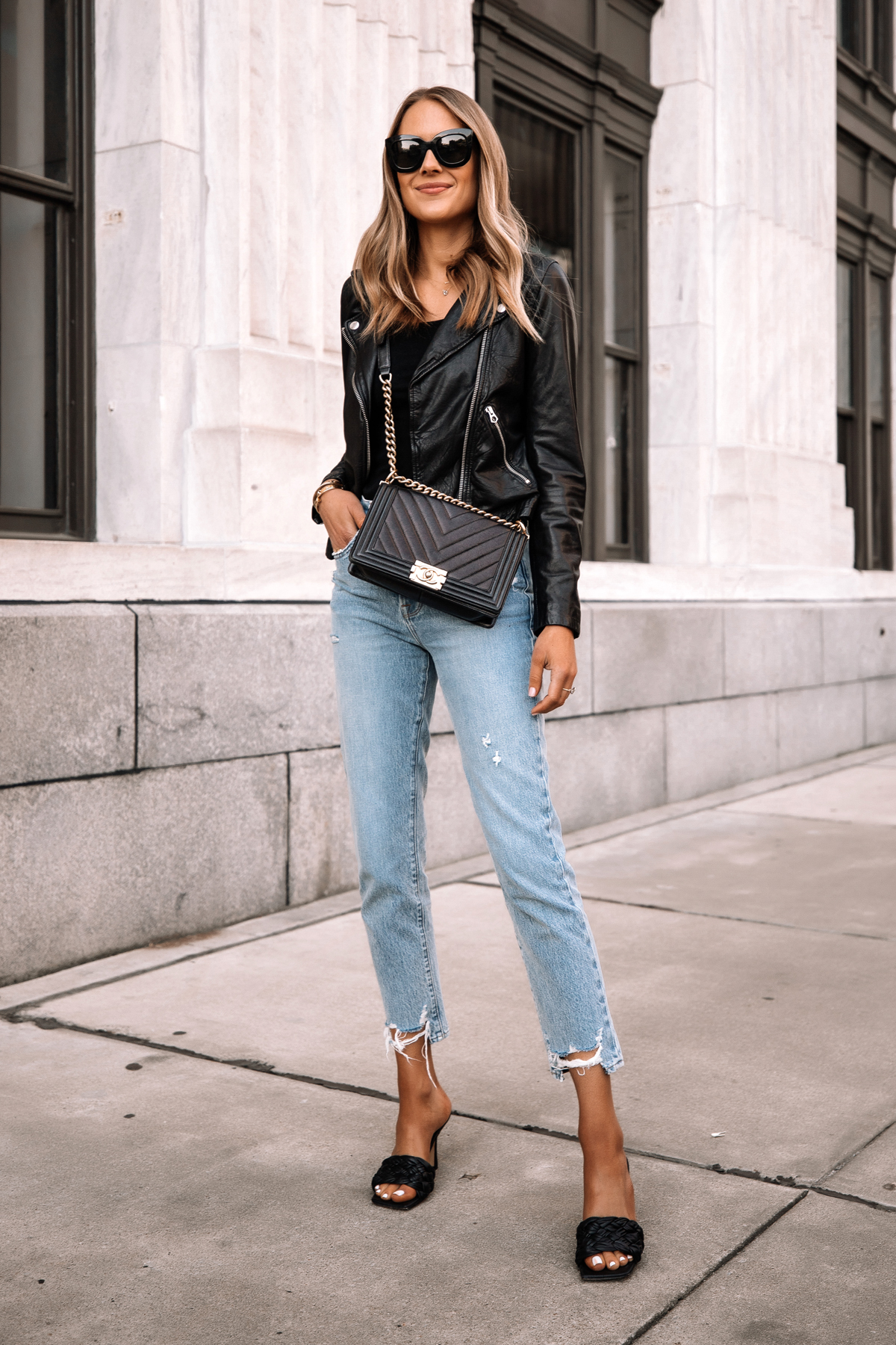 Fashion Jackson Wearing Madewell Black Leather Jacket Black Bodysuit Ripped Jeans Black Woven Heeled Sandals Chanel Black Boy Bag Street Style Outfit 2