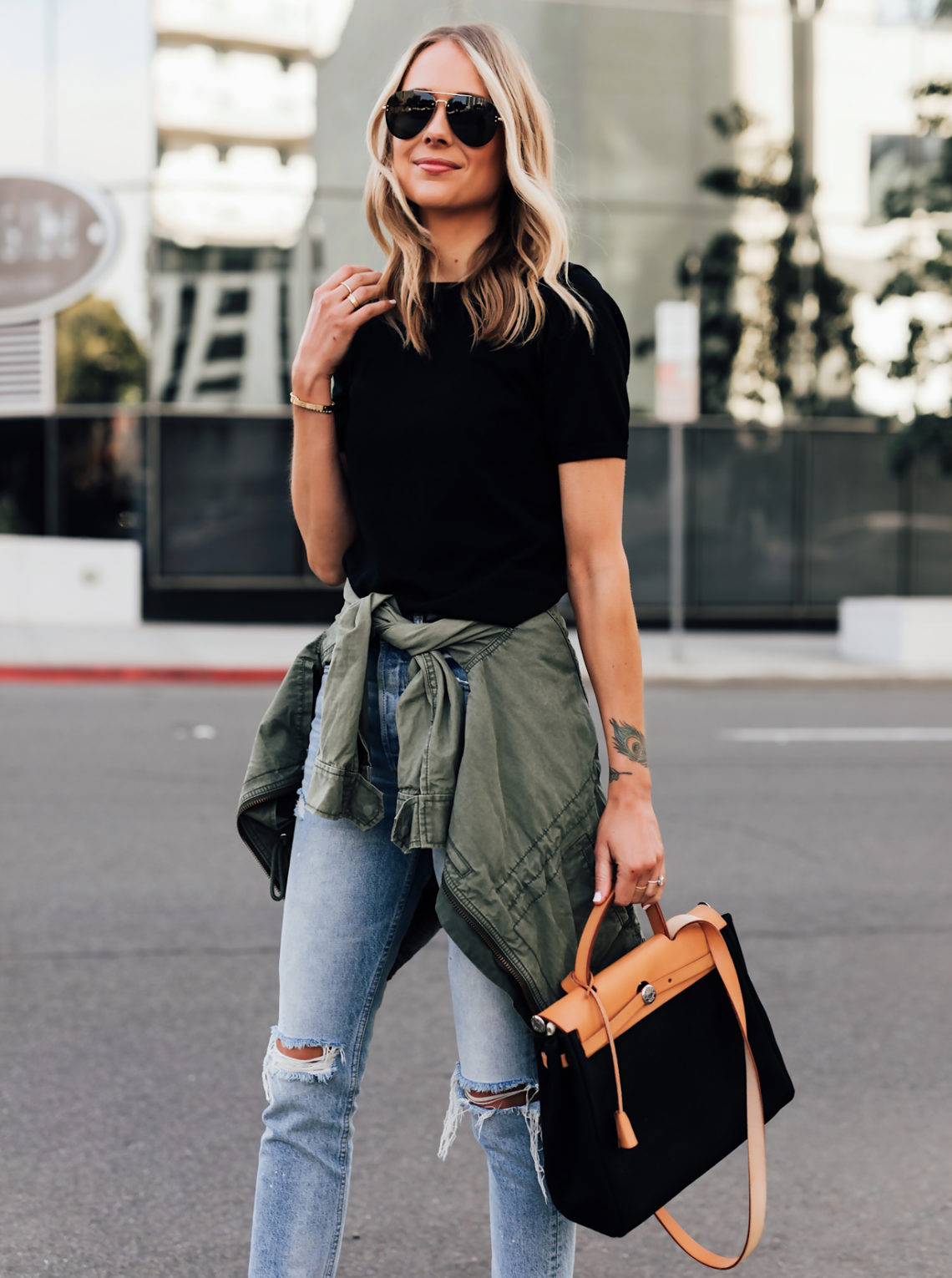 Blonde Woman Wearing Short Sleeve Black Top Denim Ripped Skinny Jeans Green Utility Jacket Vintage Hermes Herbag Black Featured Image