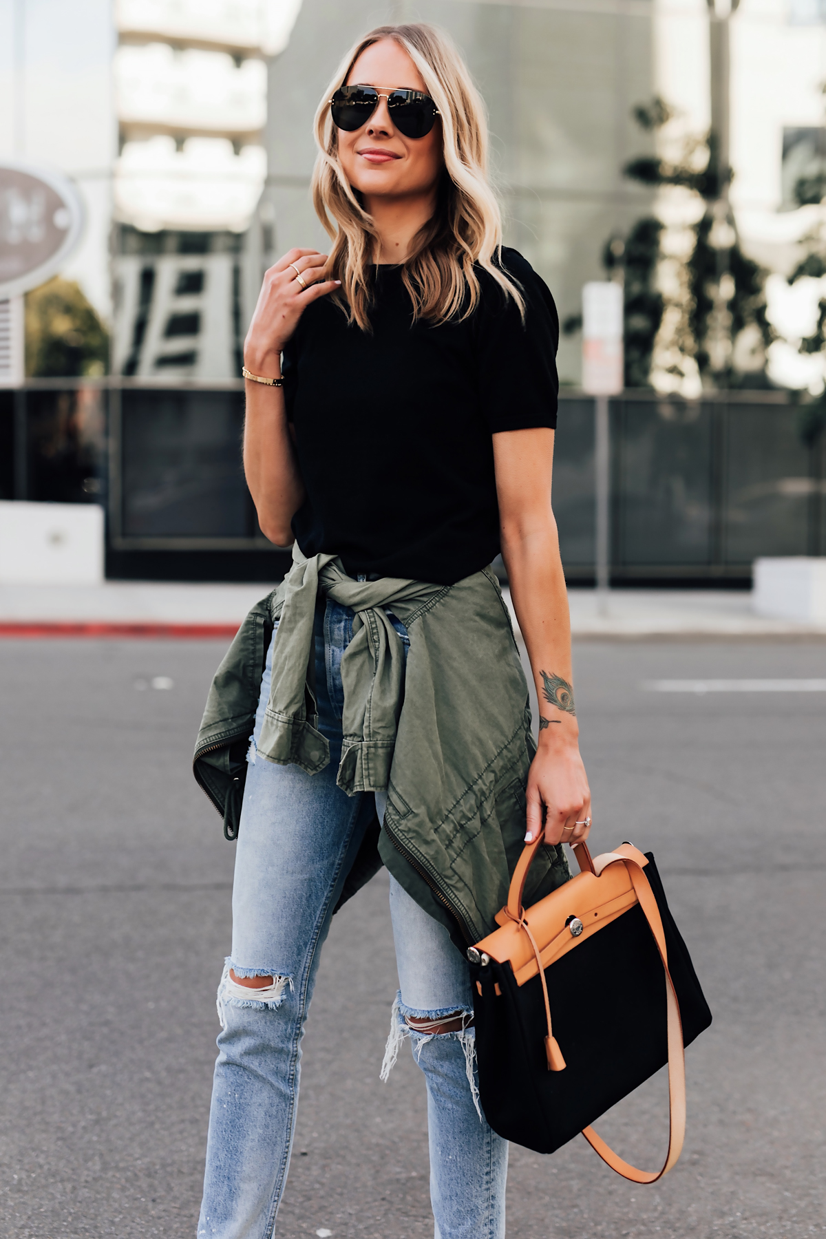 Blonde Woman Wearing Short Sleeve Black Top Denim Ripped Skinny Jeans Green Utility Jacket Vintage Hermes Herbag Black Fashion Jackson San Diego Fashion Blogger Street Style