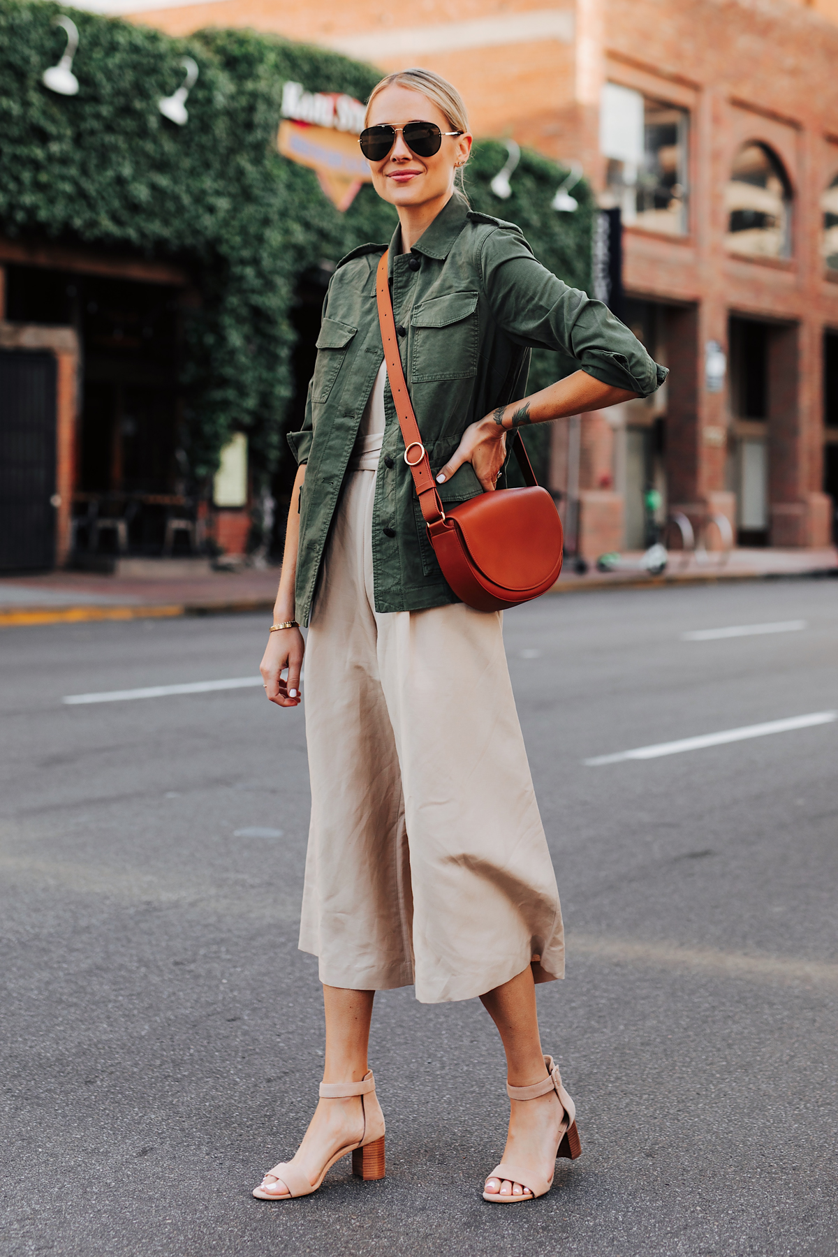Blonde Woman Wearing Banana Republic Beige Linen Jumpsuit Green Utility Jacket Tan Sandals Tan Handbag Fashion Jackson San Diego Fashion Blogger Street Style