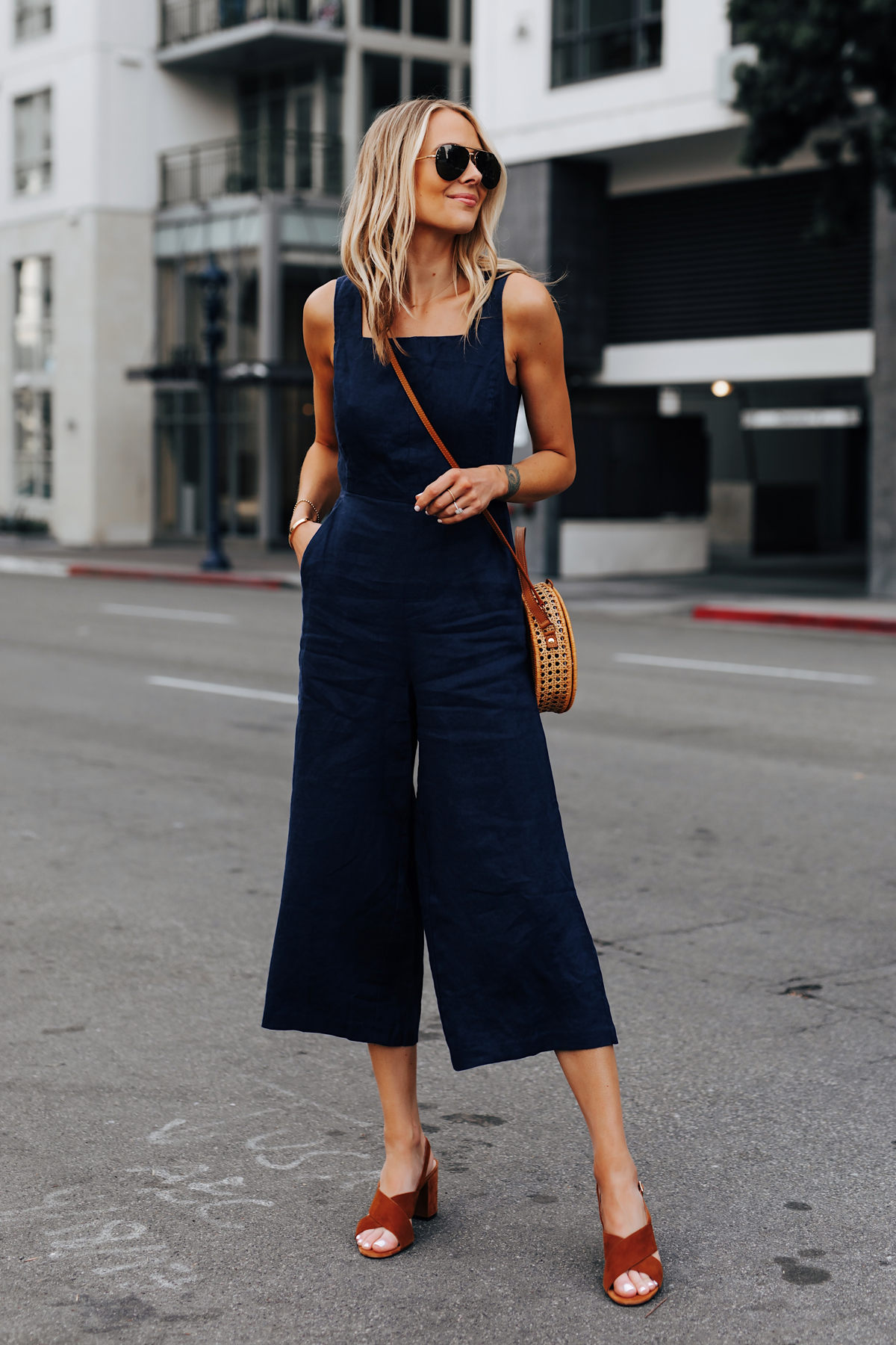 Blonde Woman Wearing Navy Open Back Jumpsuit Brown Suede Sandals Circle Basket Bag Fashion Jackson San Diego Fashion Blogger Street Style