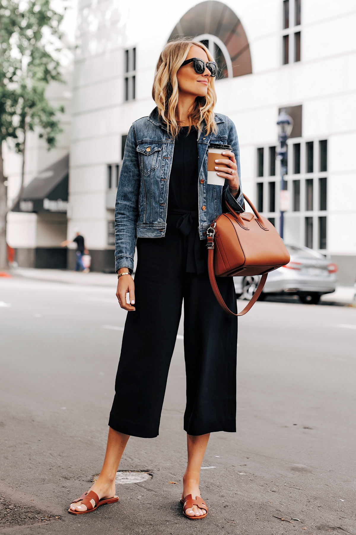 Blonde Woman Wearing Everlane Black Jumpsuit Denim Jacket Brown Sandals Brown Tote 1