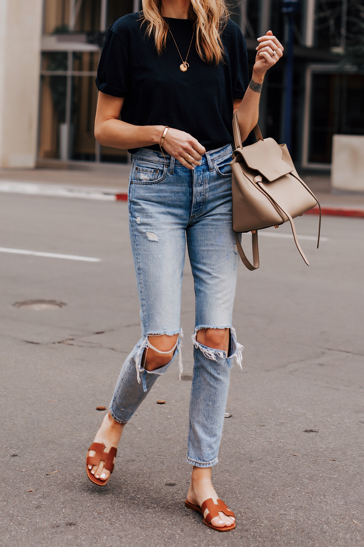 Woman Wearing Black Tshirt Ripped Jeans Hermes Oran Gold Sandals Celine Mini Belt Bag Fashion Jackson San Diego Fashion Blogger Street Style