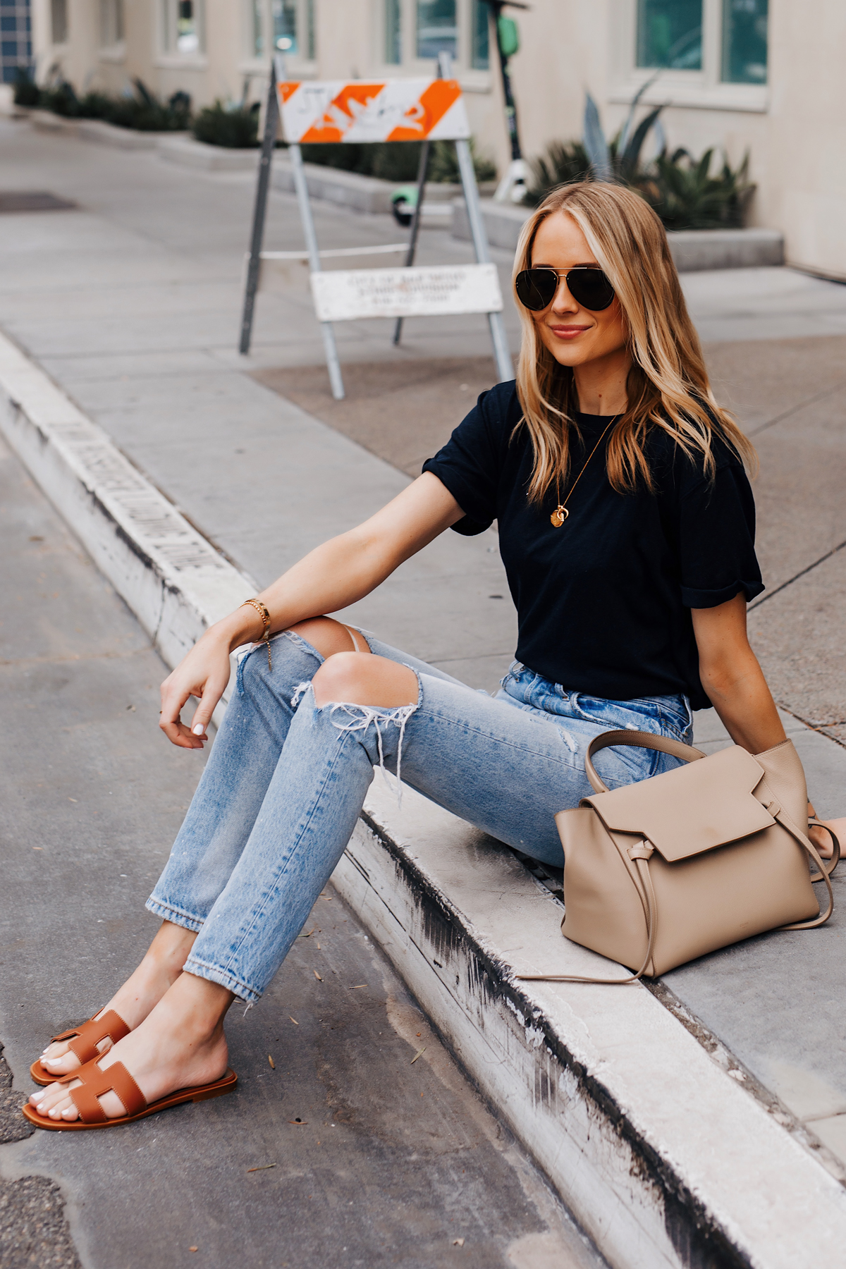 Blonde Woman Wearing Black Tshirt Ripped Jeans Hermes Oran Gold Sandals Celine Mini Belt Bag Fashion Jackson San Diego Fashion Blogger Street Style
