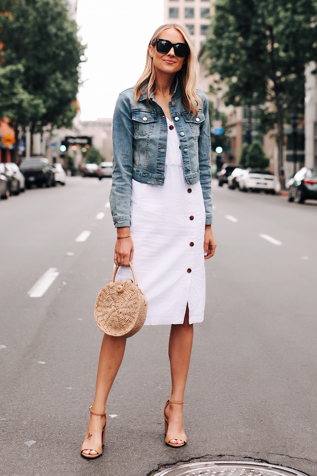Blonde Woman Wearing Denim Jacket White Midi Dress Straw Circle Handbag Tan Ankle Strap Heeled Sandals Fashion Jackson San Diego Fashion Blogger Street Style