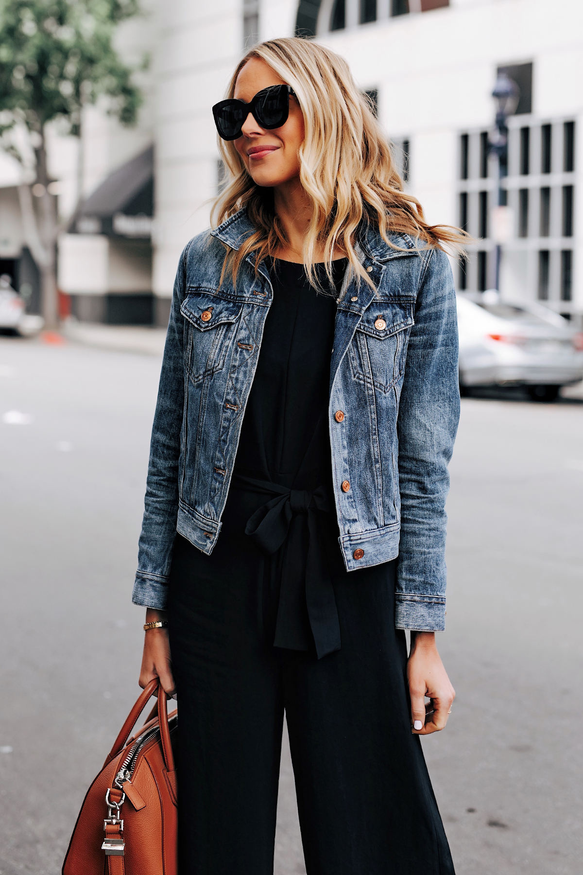 Blonde Woman Wearing Everlane Black Jumpsuit Denim Jacket Tan Tote Fashion Jackson San Diego Fashion Blogger Street Style