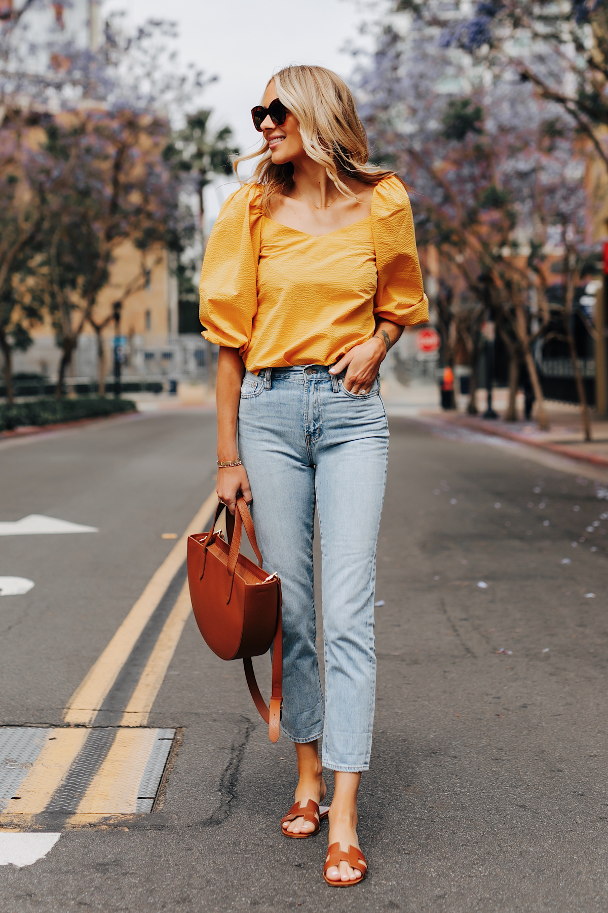 Fashion Jackson Wearing Cuyana Yellow Blouse Denim Ankle Jeans Hermes Oran Gold Sandals Cuyana Tan Handbag