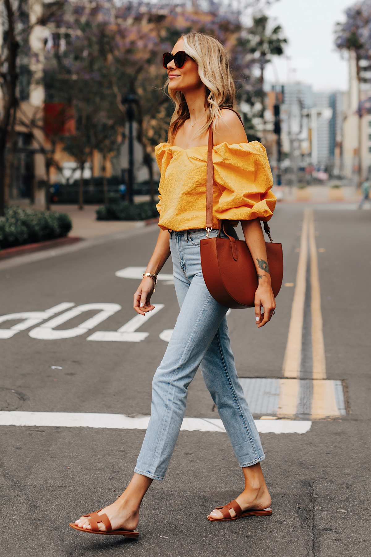 Fashion Jackson Wearing Cuyana Yellow Off the Shoulder Blouse Denim Ankle Jeans Hermes Oran Gold Sandals Cuyana Tan Handbag
