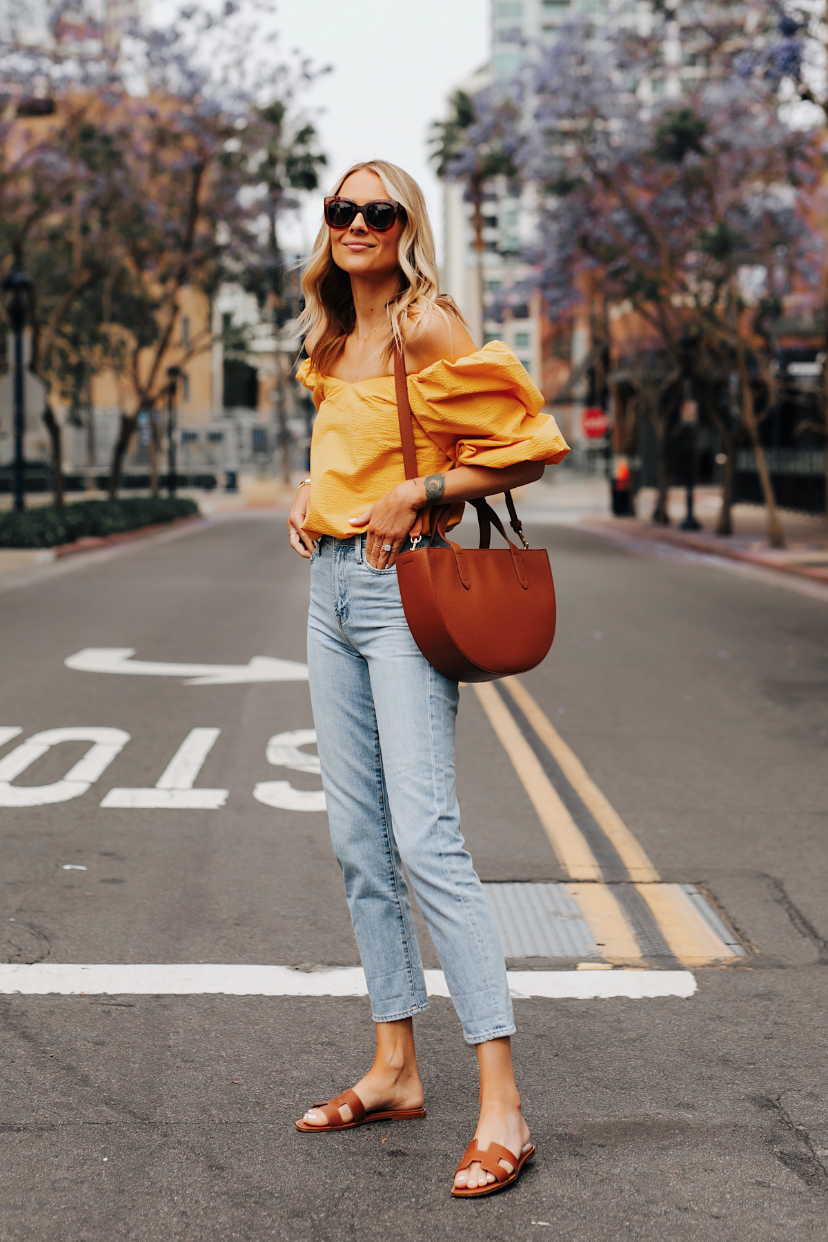 Fashion Jackson Wearing Cuyana Yellow Off the Shoulder Blouse Denim Ankle Jeans Hermes Oran Gold Sandals Cuyana Tan Semi Circle Handbag