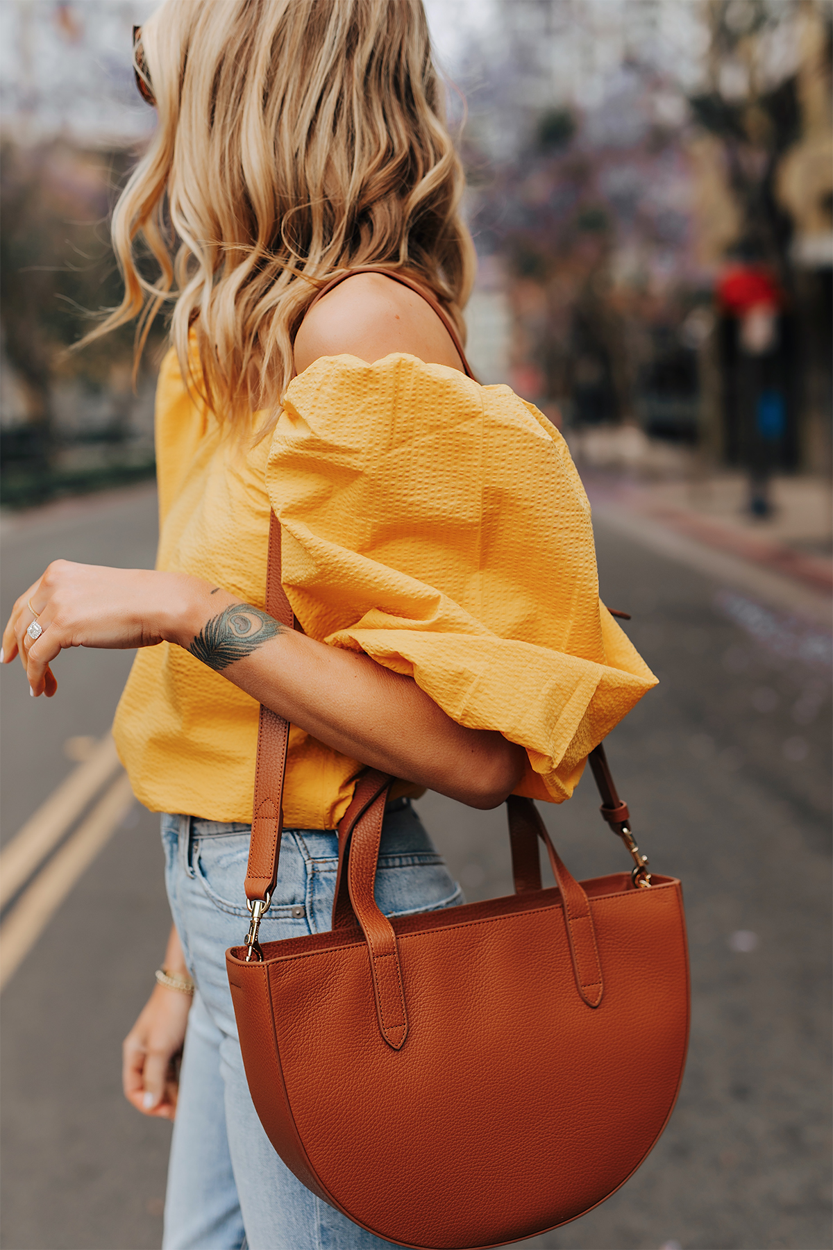 Fashion Jackson Wearing Cuyana Yellow Off the Shoulder Blouse Jeans Cuyana Tan Semi Circle Handbag