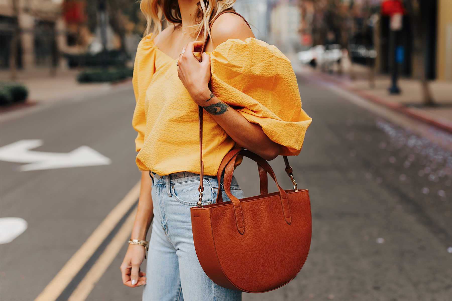 Fashion Jackson Wearing Cuyana Yellow Off the Shoulder Blouse Light Wash Jeans Cuyana Tan Semi Circle Handbag