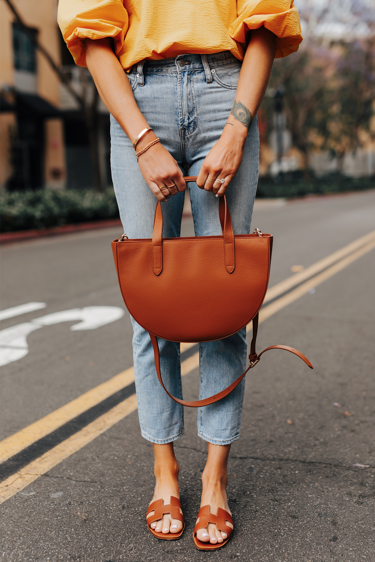 Fashion Jackson Wearing Denim Ankle Jeans Hermes Oran Gold Sandals Cuyana Tan Semi Circle Handbag