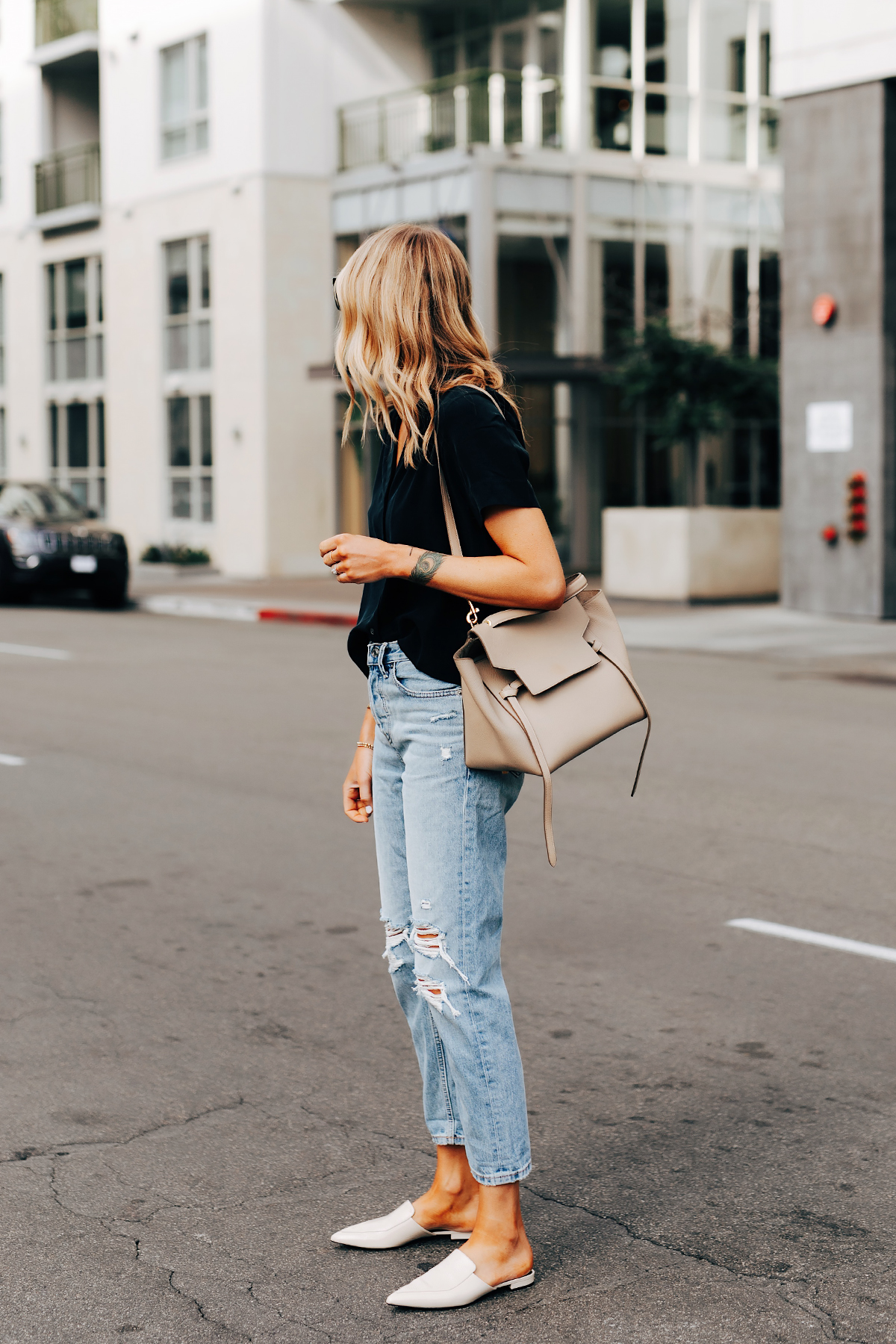 Fashion Jackson Wearing Everlane Short Sleeve Black Top Everlane Ripped Boyfriend Jeans Everlane White Mules Celine Belt Bag