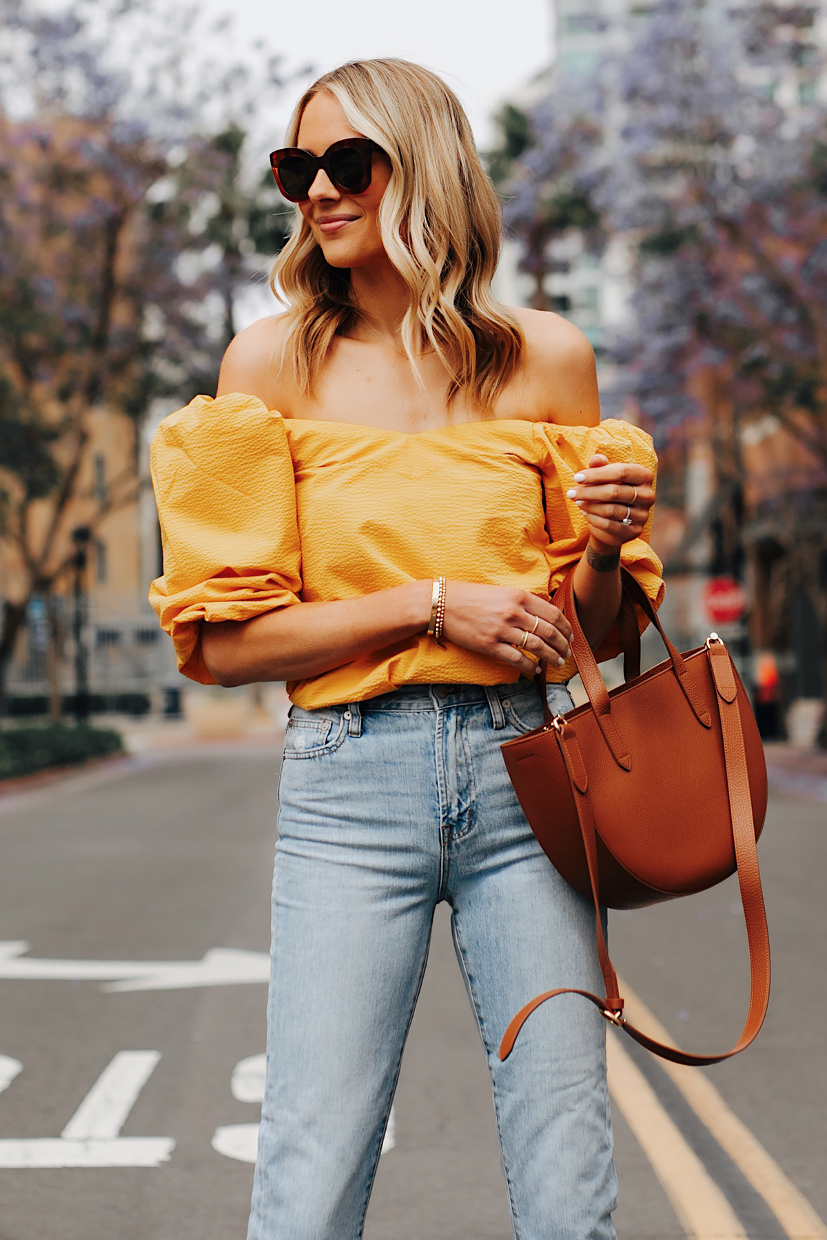 Fashion Jackson Wearing Cuyana Yellow Off the Shoulder Top Light Wash Jeans Cuyana Tan Semi Circle Handbag
