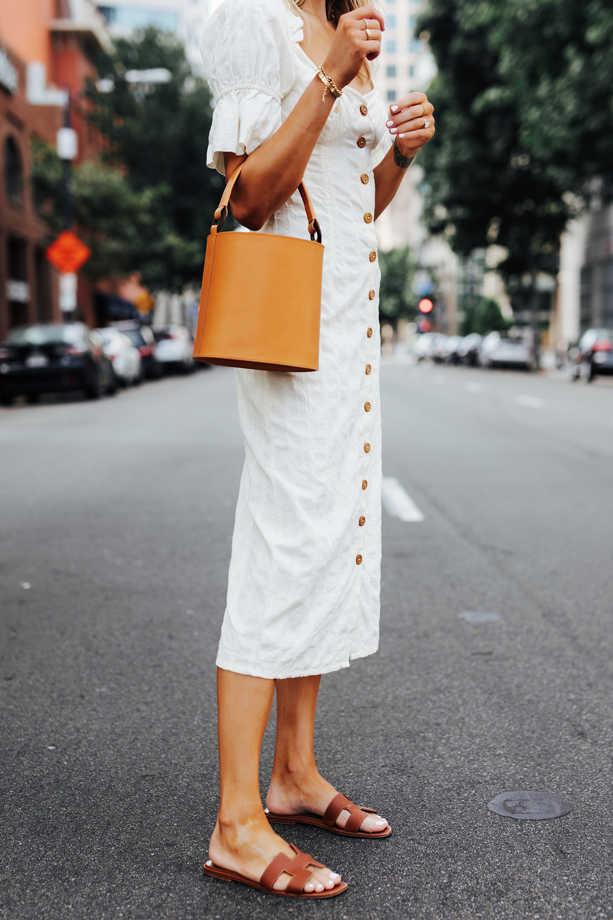 Fashion Jackson Wearing Free People White Off The Shoulder Button Front Midi Dress Tan Bucket Bag Hermes Oran Gold Sandals