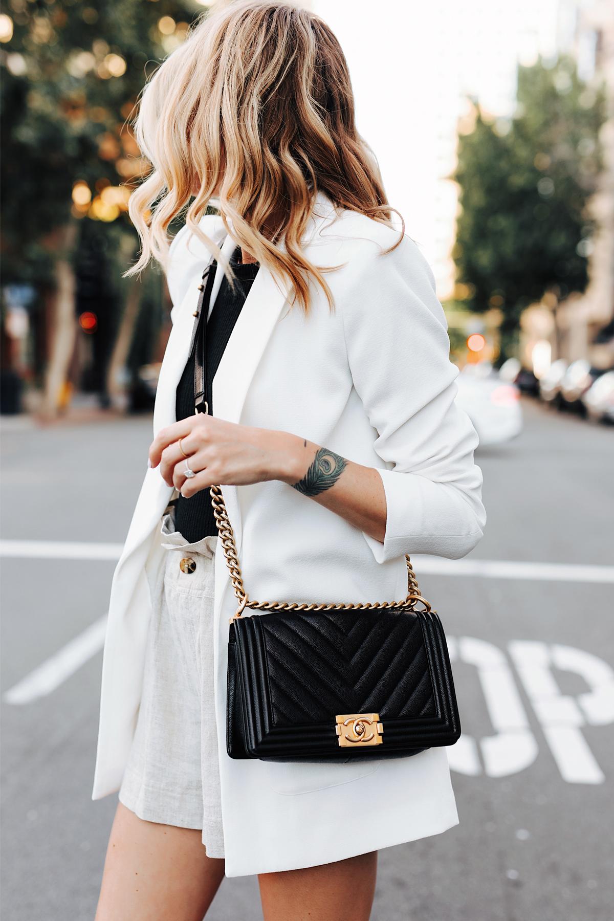 Fashion Jackson Wearing Long White Blazer Black Top Tan Linen Shorts Chanel Black Boy Bag 1