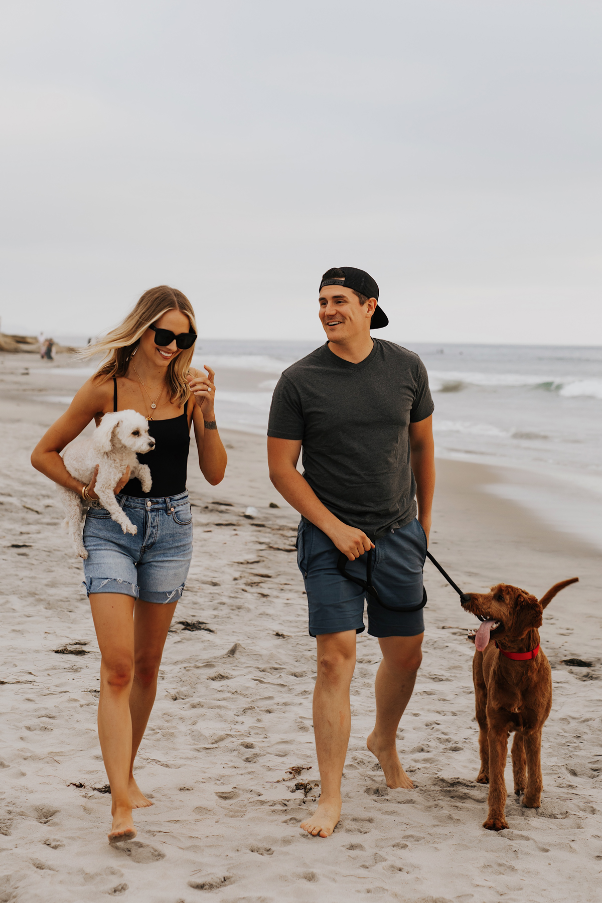 Fashion Jackson Wearing Black One Piece Swimsuit Long Denim Shorts Will Wearing Tshirt Roark Shorts with dogs at San Diego Dog Beach