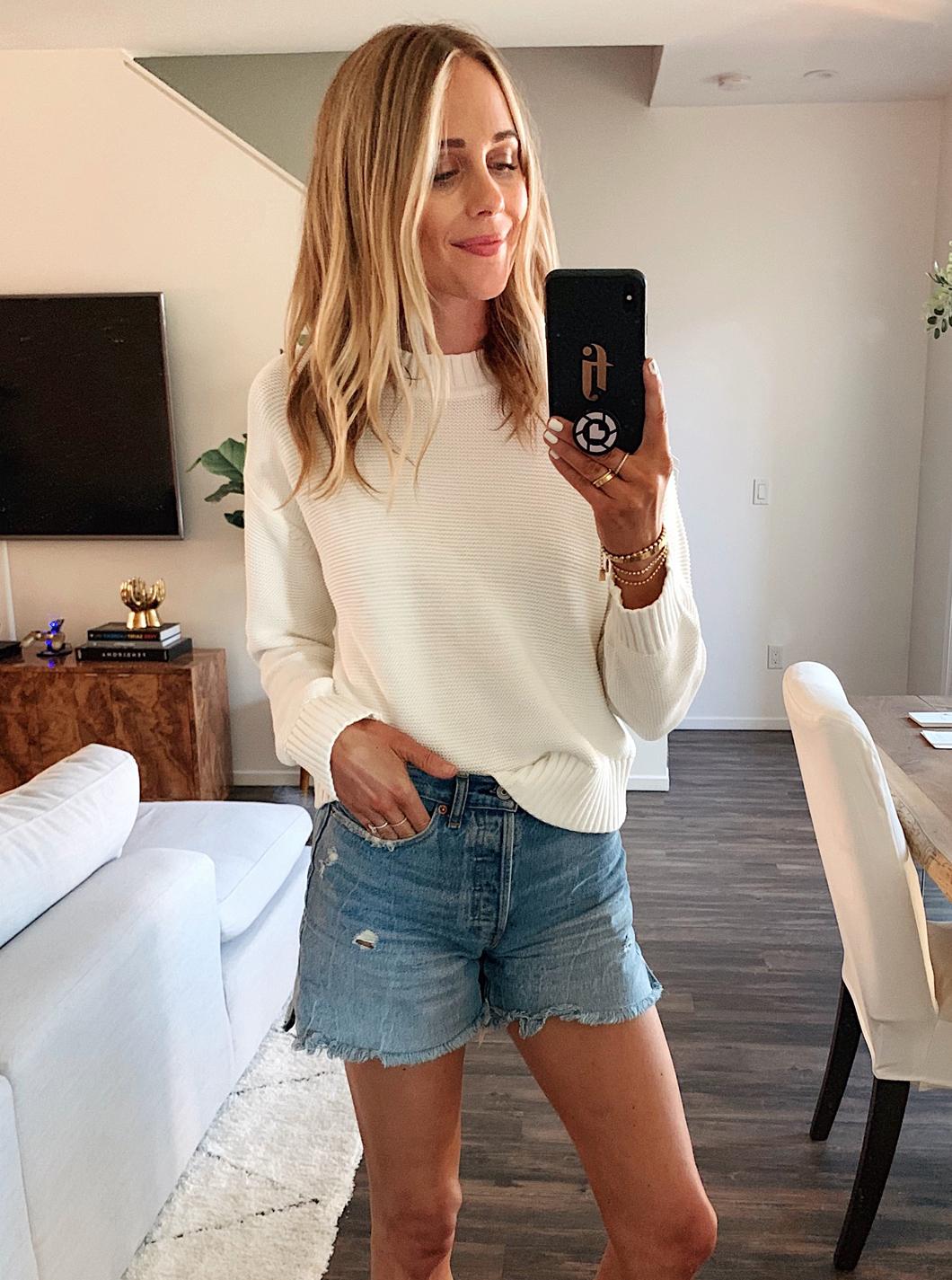 Fashion Jackson Wearing Everlane White Sweater Denim Shorts