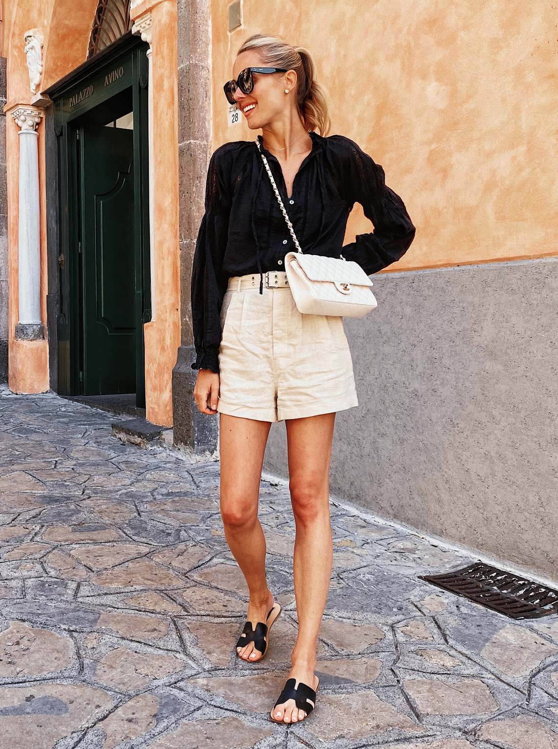 Fashin Jackson Wearing Black Peasant Blouse Khaki Shorts Black Sandals White Chanel Handbag Italy Summer Outfit