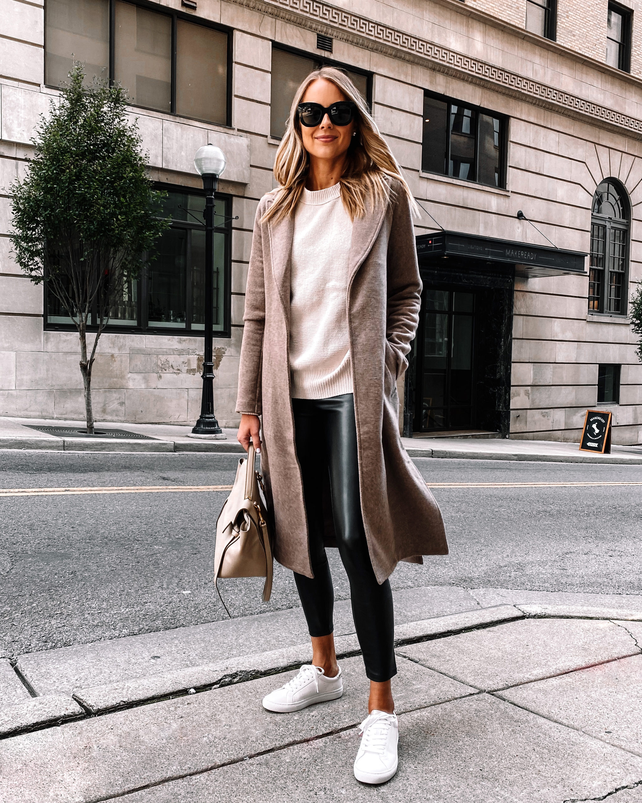 Fashion Jackson Wearing Beige Wool Wrap Coat White Sweater Black Faux Leather Leggings White Sneakers Fall Outfit