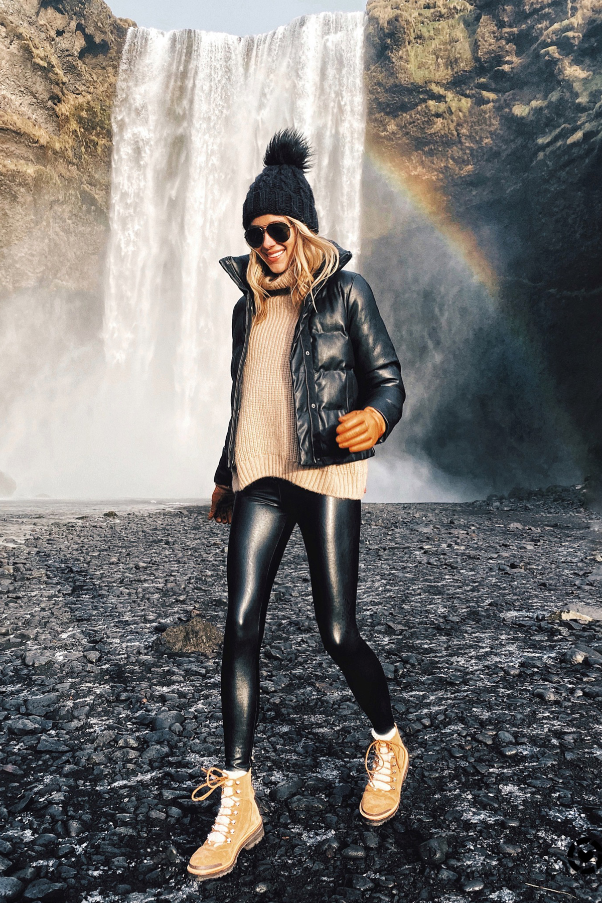 Fashion Jackson Wearing Black Puffer Jacket Black Faux Leather Leggings Winter Boots Black Beanie Outfit Skogafoss Waterfall Iceland Itinerary