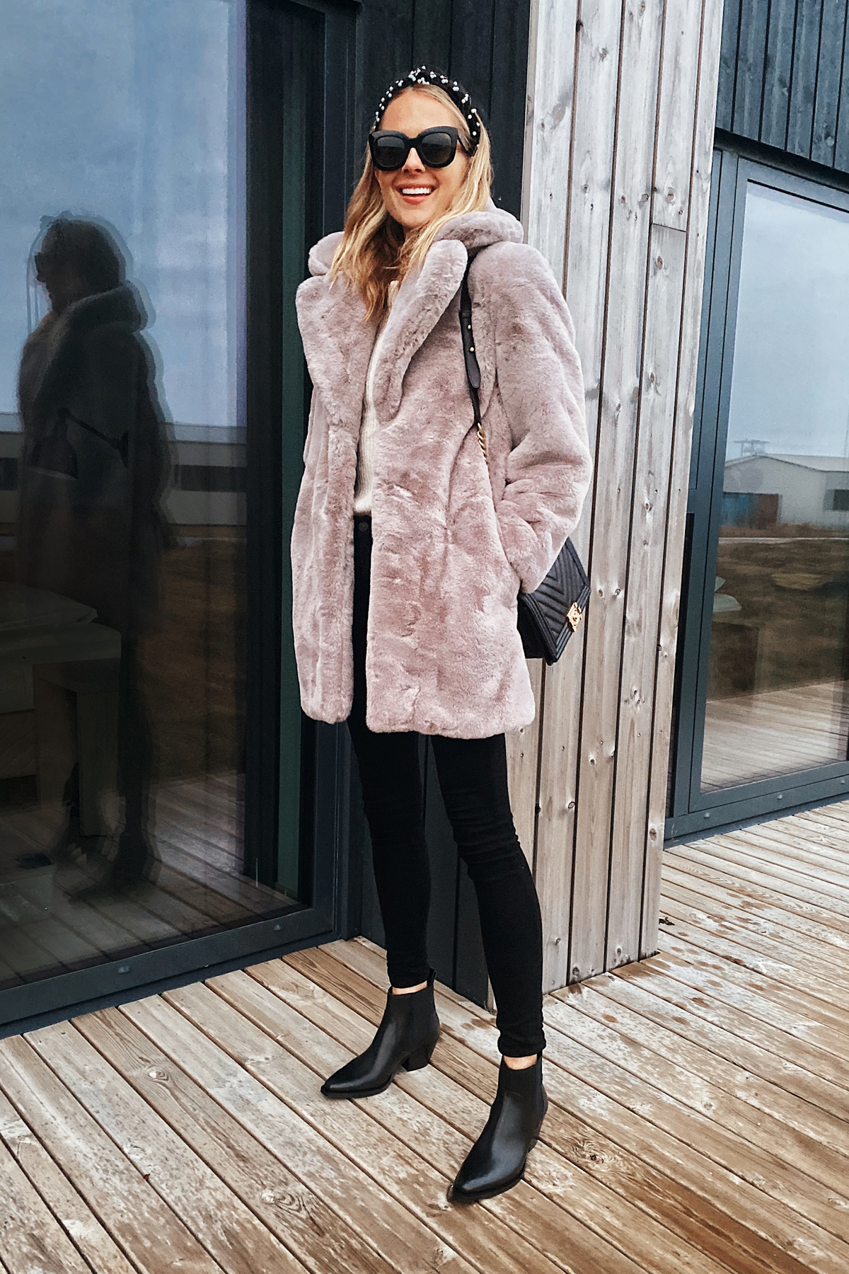 Fashion Jackson Wearing Grey Faux Fur Coat Black Pants Black Boots Iceland Itinerary Travel Guide