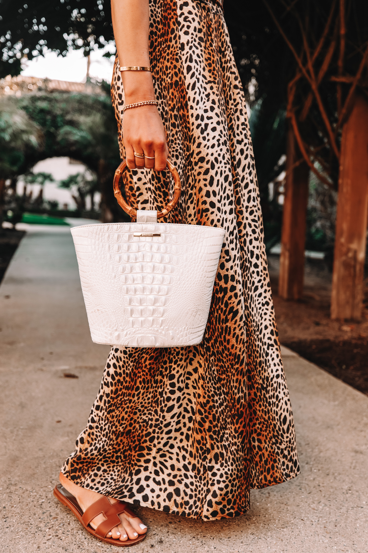 Fashion Jackson Wearing Leopard Maxi Dress Holding Brahmin Mod Bowie Handbag in White Hermes Oran Sandals Brown