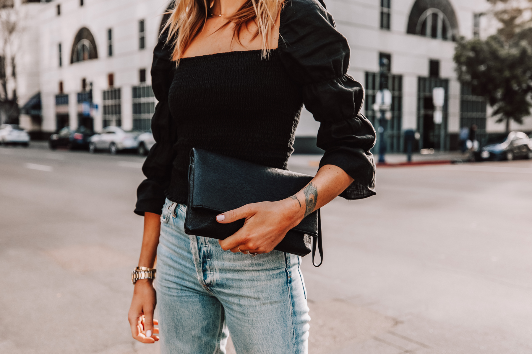 Fashion Jackson Wearing Black Puff Sleeve Rouched Top Black Clutch Jeans