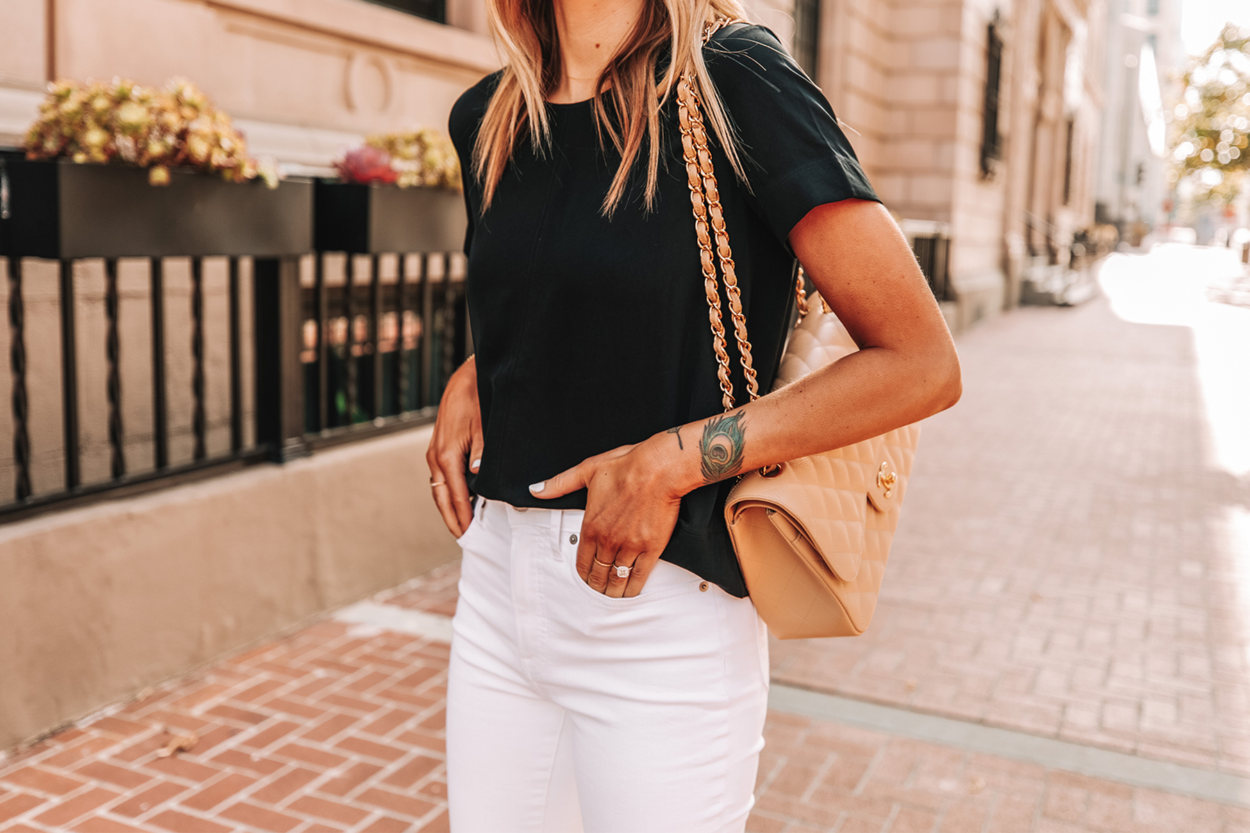 Fahsion Jackson Wearing Everlane Black Short Sleeve Top White High Rise Jeans Chanel Beige Handbag