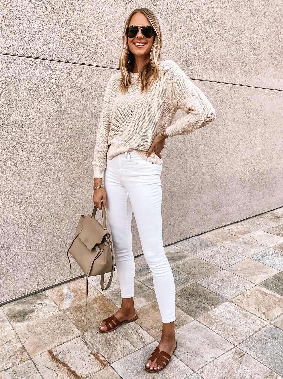 Fashion Jackson wearing Everlane white jeans, Everlane beige sweater, Celine mini belt bag, brown sandals
