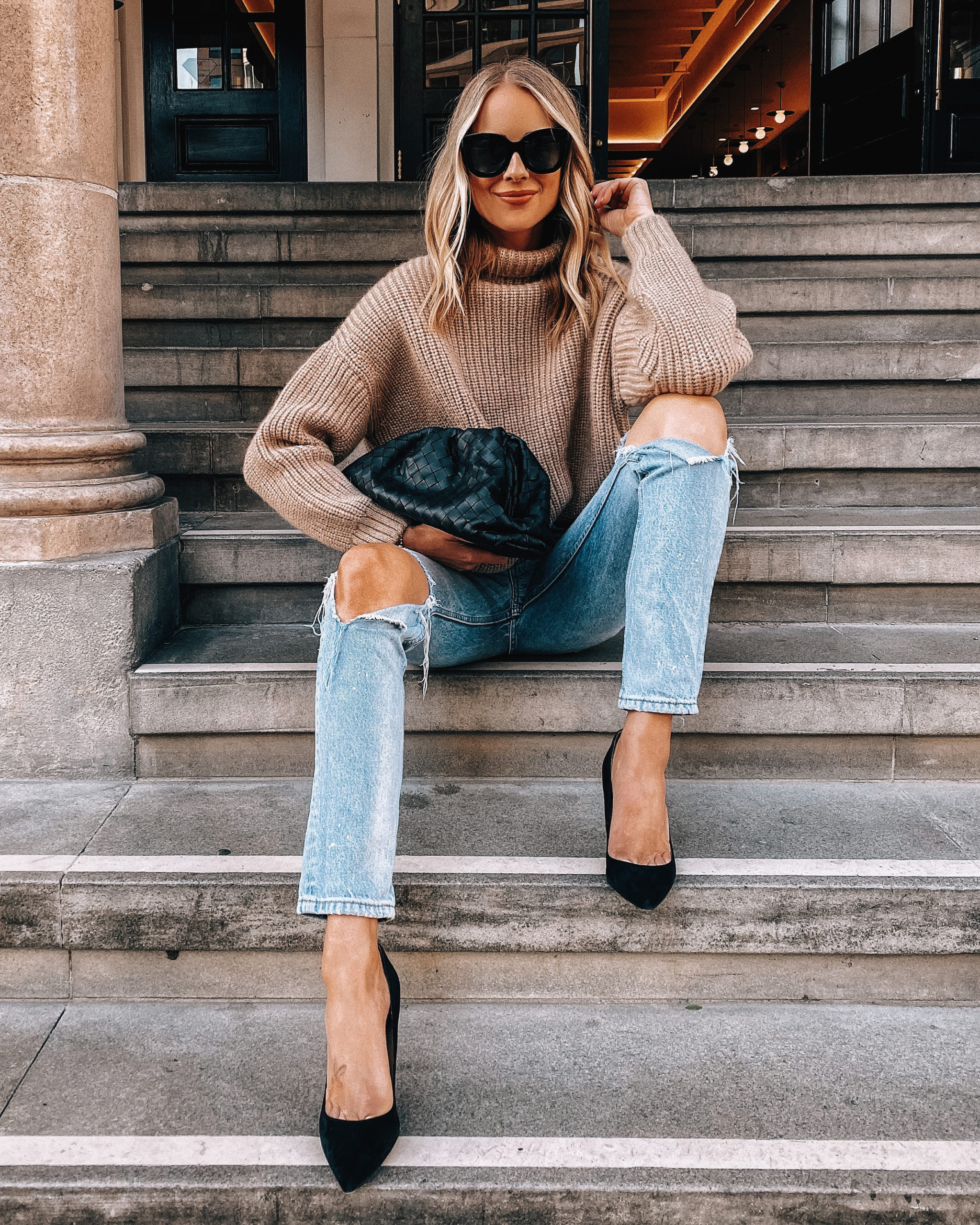 Fashion Jackson Wearing Oversized Tan Sweater Ripped Jeans Black Pumps Bottega Venta Black Clutch