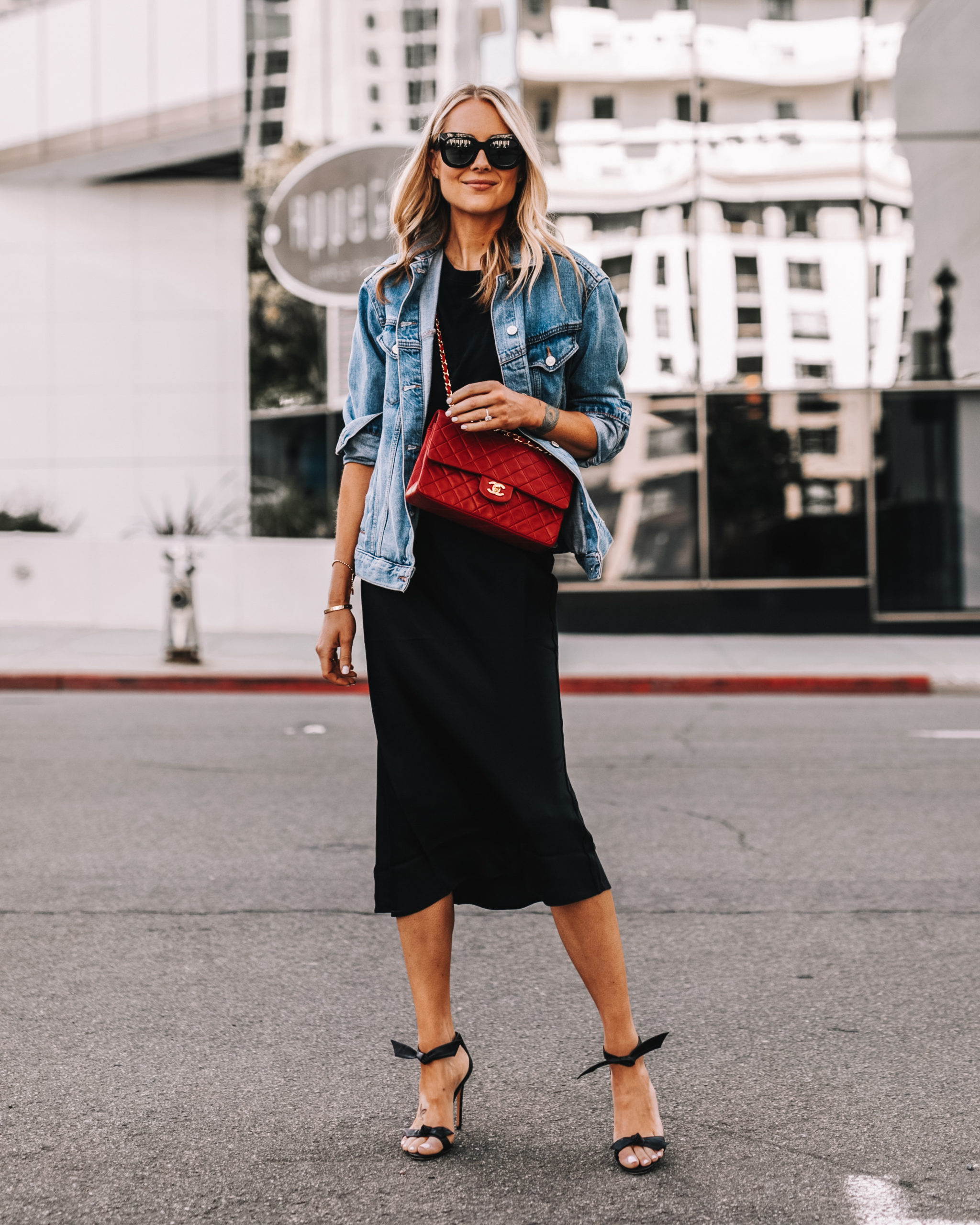 fashion jackson wearing oversized denim jacket black slip skirt red chanel handbag