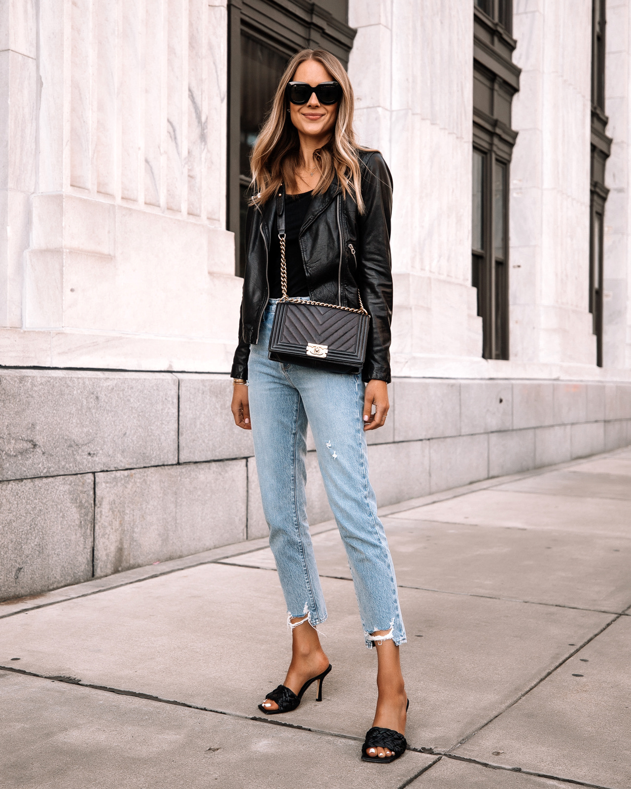 Fashion Jackson Wearing Madewell Black Leather Jacket Black Bodysuit Ripped Jeans Black Woven Heeled Sandals Chanel Black Boy Bag Street Style Outfit