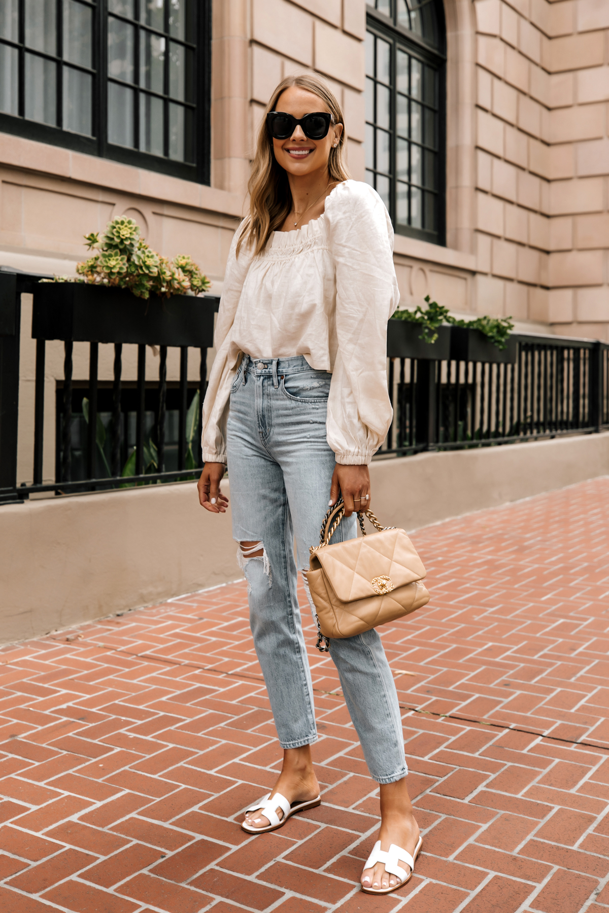 Fashion Jackson Wearing Beige Linen Puff Sleeve Top Madewell Ripped Jeans Hermes White Sandals Chanel 19 Beige Handbag 1
