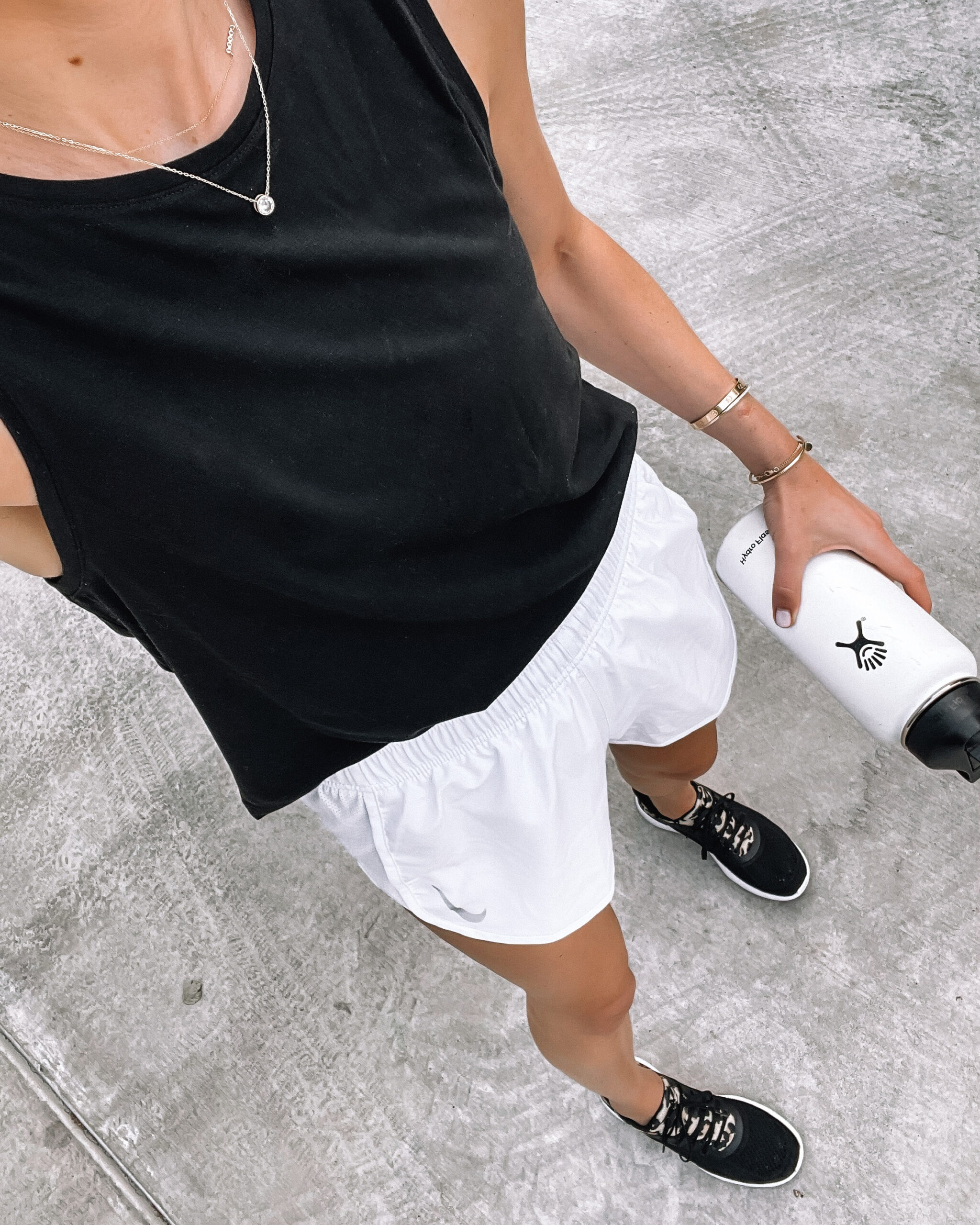Fashion Jackson Wearing Black Muscle Workout Tank White Nike Running Shorts With Liner APL Black Leopard Sneakers White Hydroflask Womens Workout Outfit