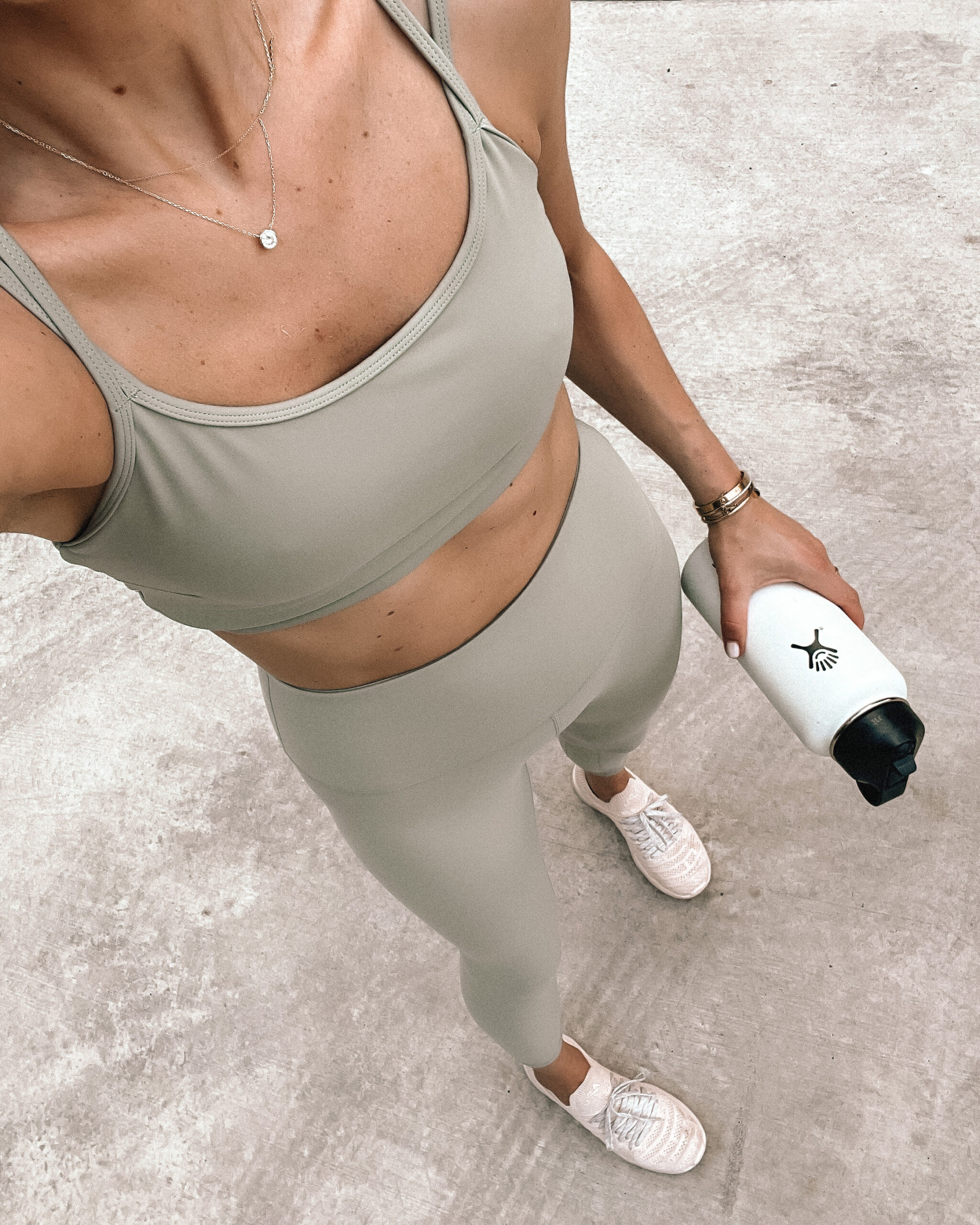 Fashion Jackson Wearing Varley Light Green Strappy Sports Bra Varley Light Green Leggings Blush APL Sneakers White Hydroflask Womens Workout Outfit