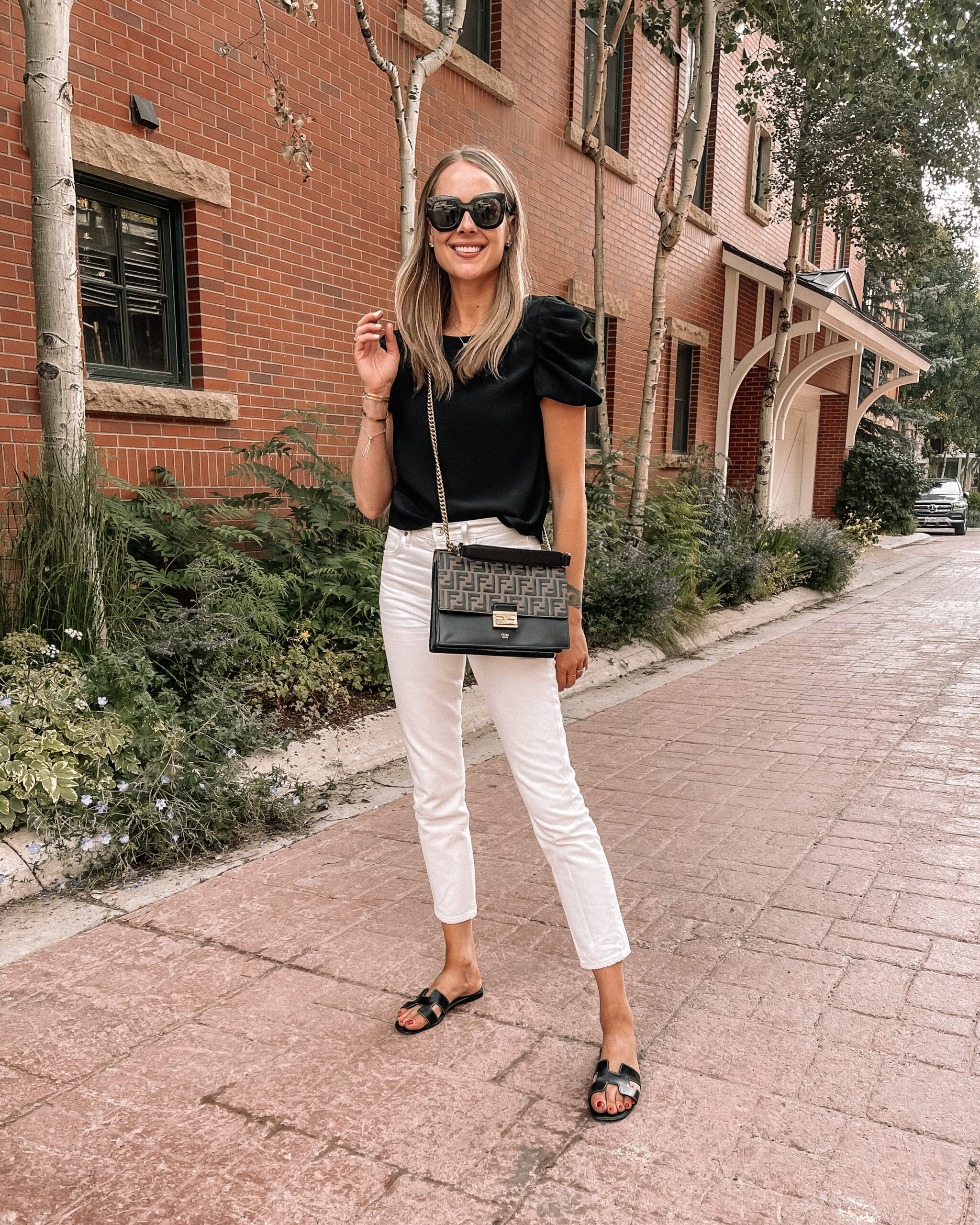 Fashion Jackson Wearing Amanda Uprichard Black Puff Sleeve Top Citizens of Humanity White Jeans Hermes Oran Black Sandals Telluride Summer Outfit