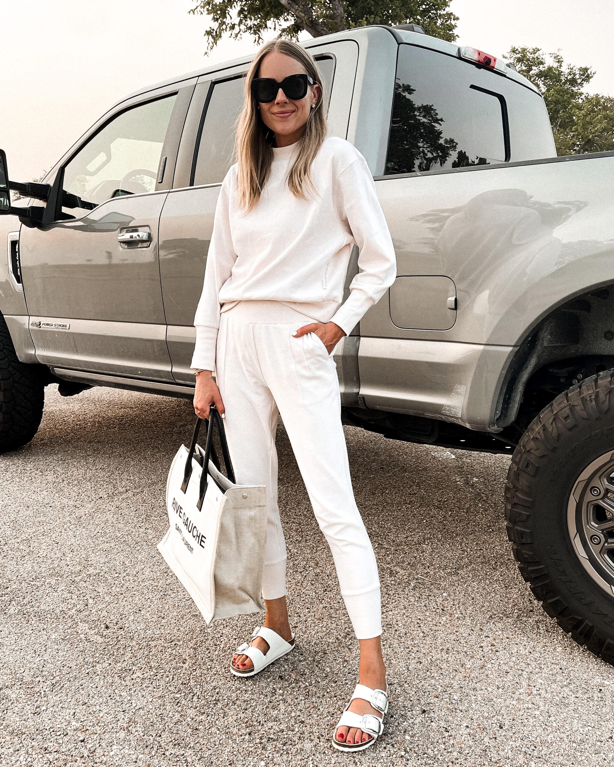 Fashion Jackson Wearing Ivory Sweatshirt Ivory Joggers White Birkenstock Sandals Saint Laurent Canvas Tote Travel Outfit