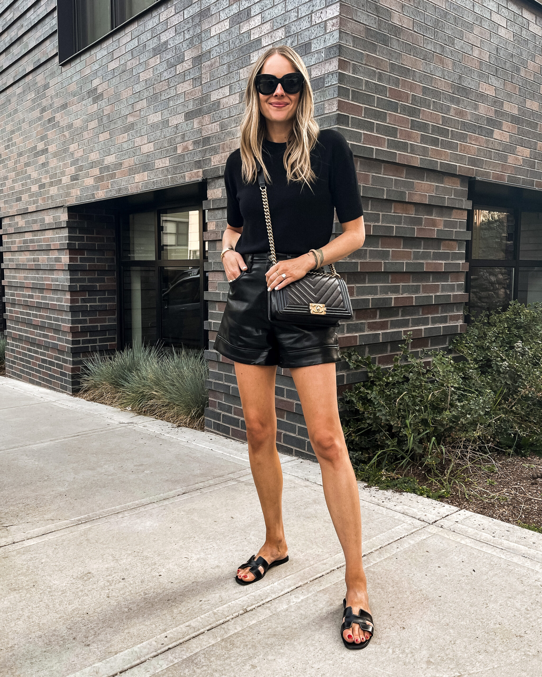 Fashion Jackson Wearing Theory Black Short Sleeve Cashmere Sweater AGOLDE Black Leather Shorts Hermes Oran Black Sandals Telluride Summer Outfit